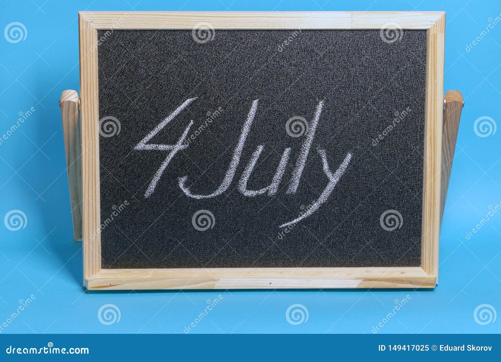 Le tableau noir avec le mot a marqué à la craie le 4ème juillet sur le fond bleu