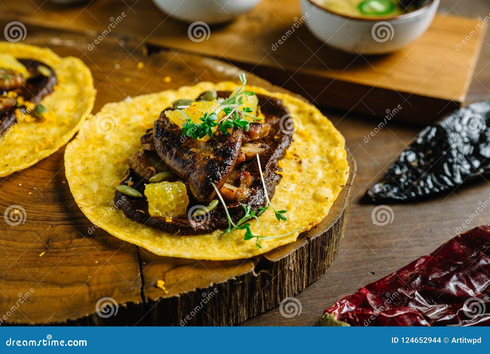 Le Tacos de Foie Gras a servi sur le hachoir en bois avec différentes sauces et le Mexicain a séché le piment