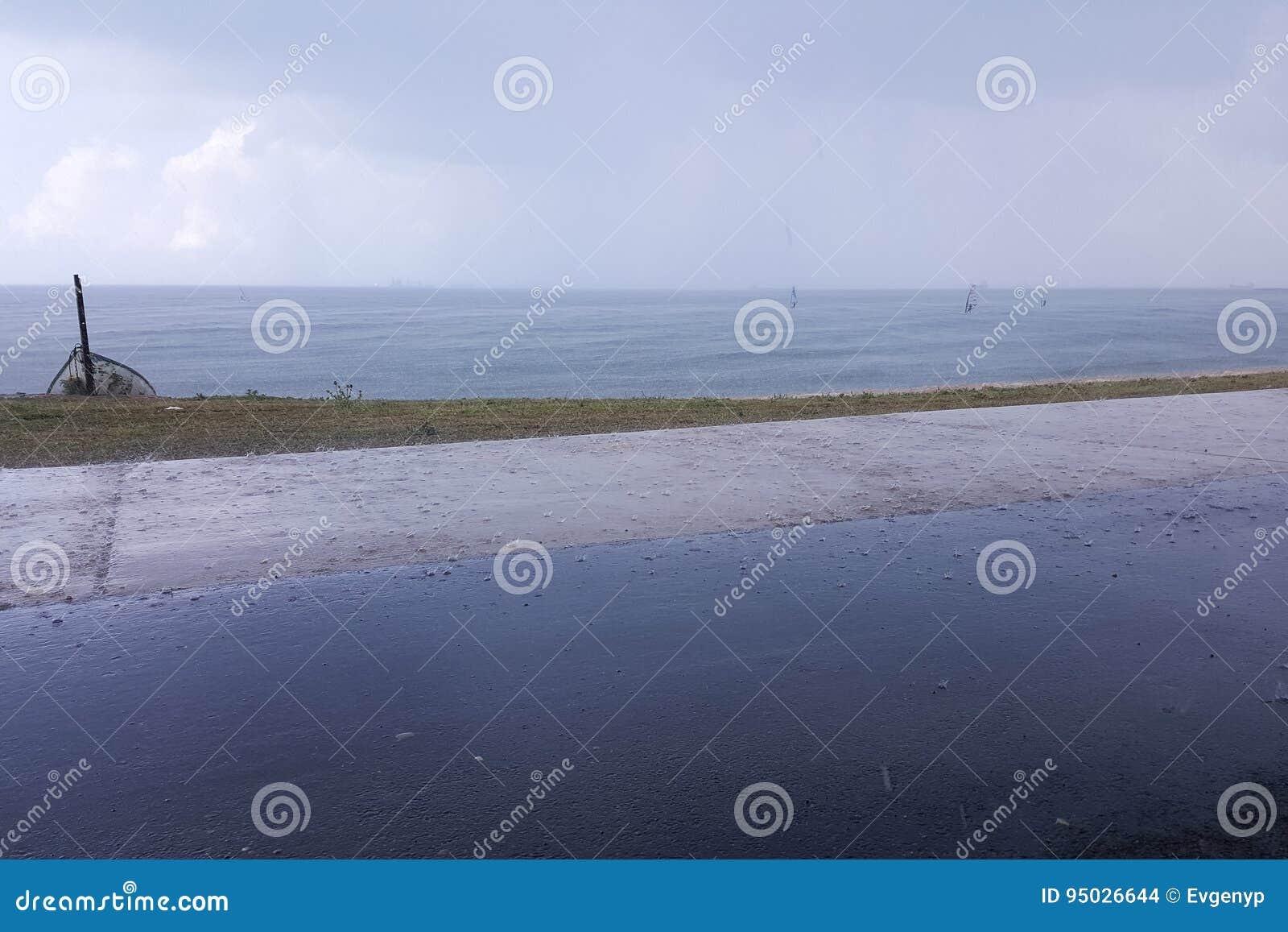 Le temps nuageux sur le bord de la mer, surfers montent sous la pluie, accrochant opacifie