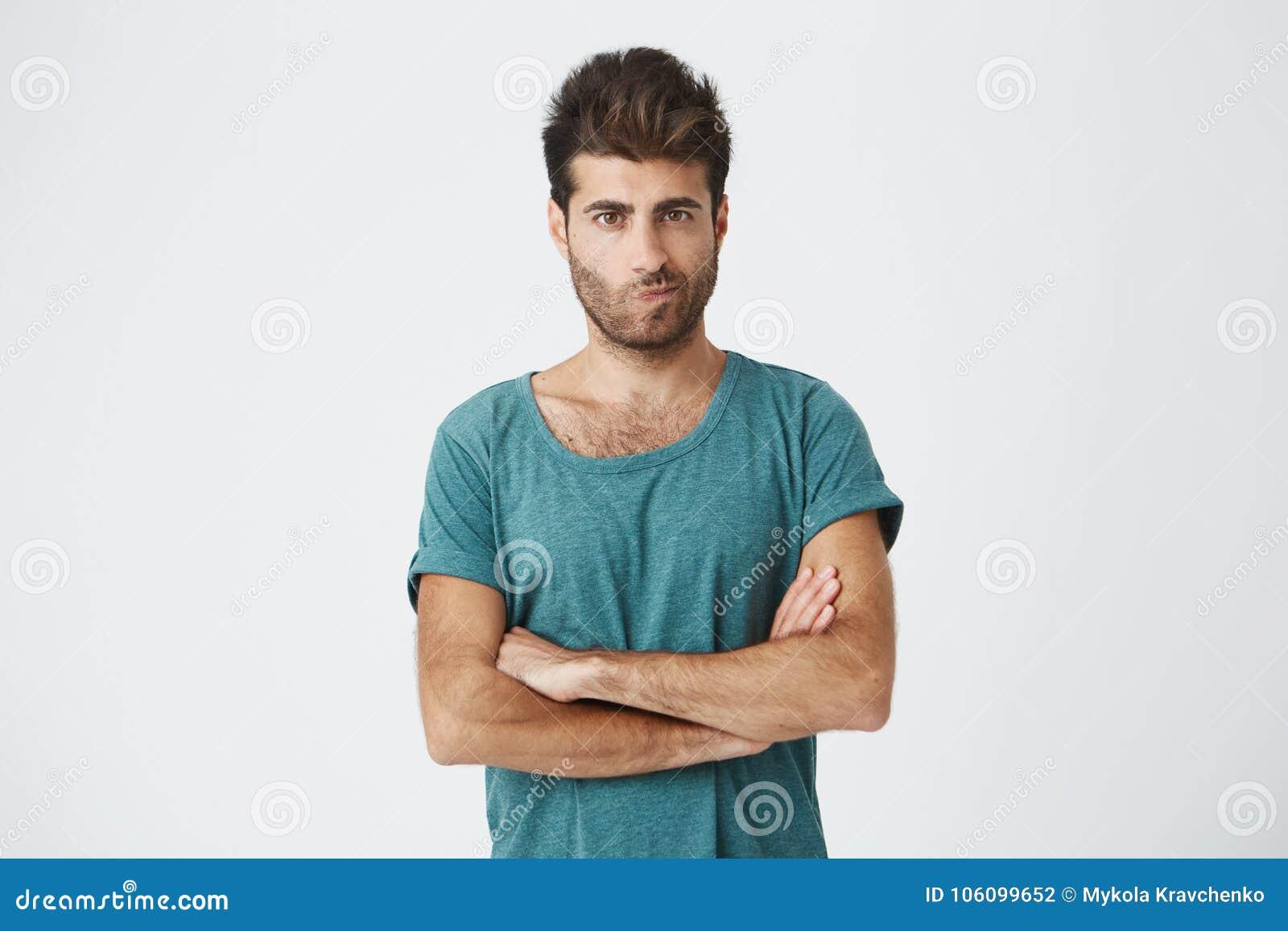 Le tir d isolement de l homme fâché utilisant le T-shirt bleu avec la coiffure élégante tenant des bras a croisé, ayant sceptique