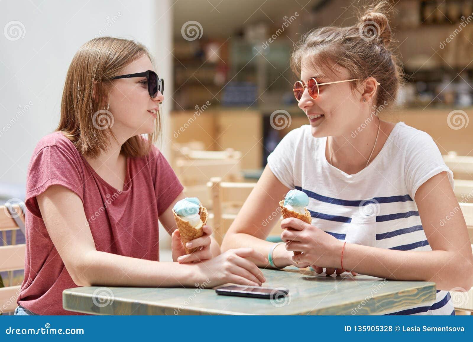 Le tir horizontal de deux filles européennes gaies utilise les lunettes de soleil à la mode, mange la crème glacée froide, se rep