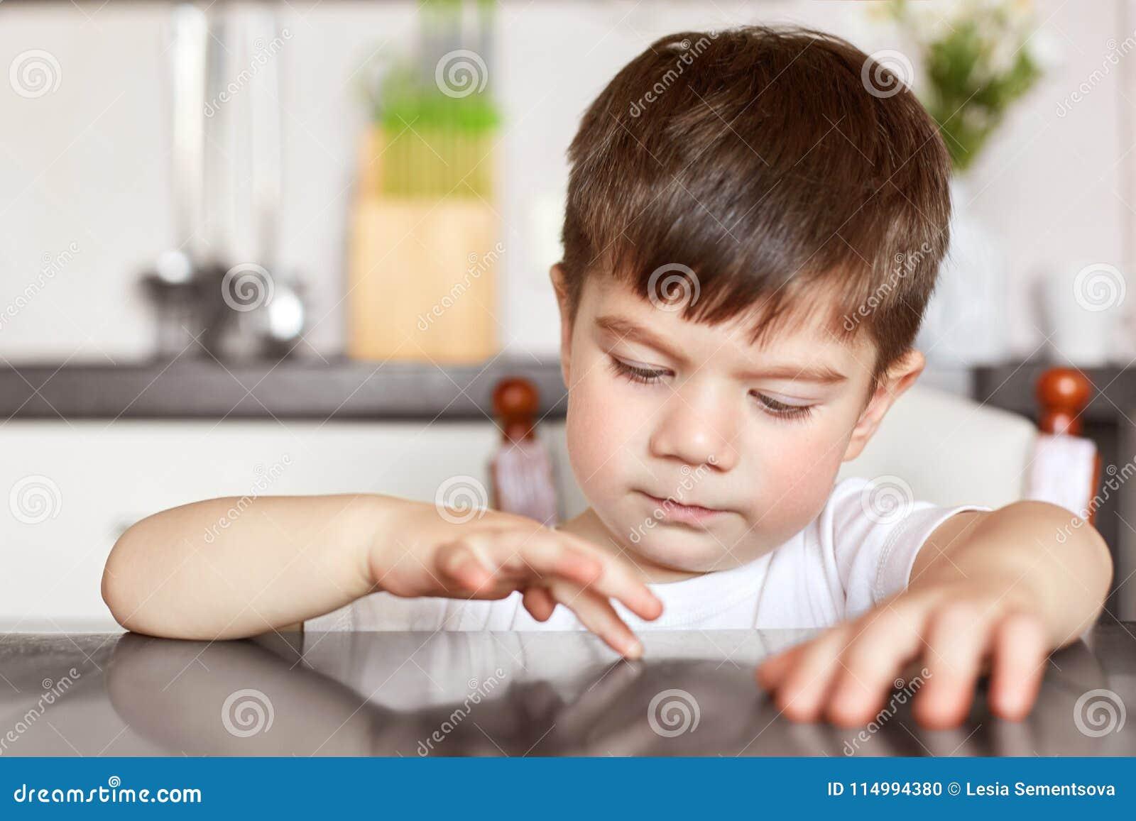 Le tir horizontal de l enfant masculin châtain bel touche la table de cuisine, étant curieux, se sent ennuyé et affamé tandis que