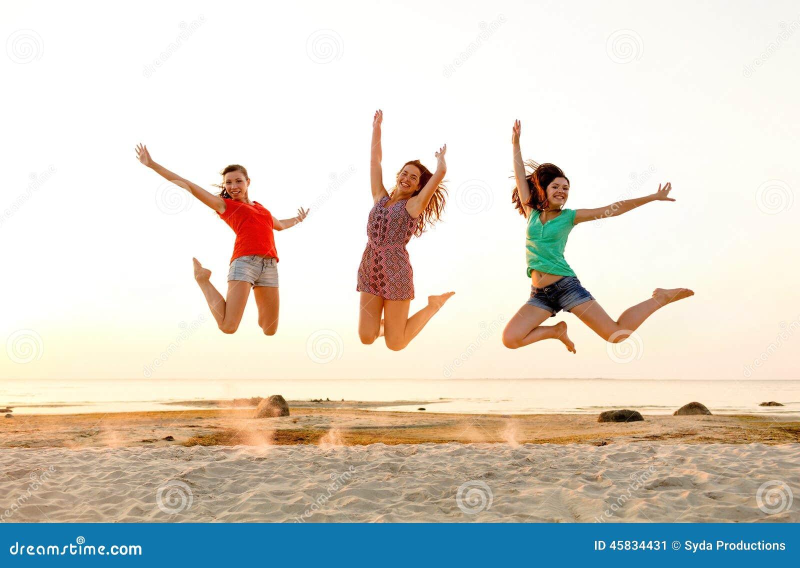 Le tonåriga flickor som hoppar på stranden