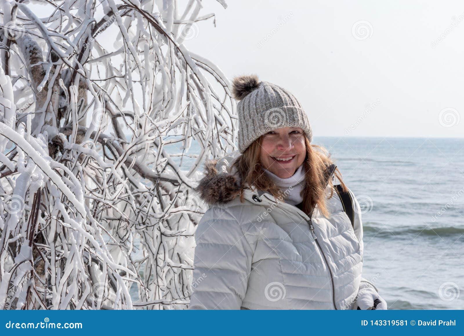 Le touriste de sourire posant à côté de la glace a couvert des branches d arbre au parc de point de caverne, le comté de Door, le