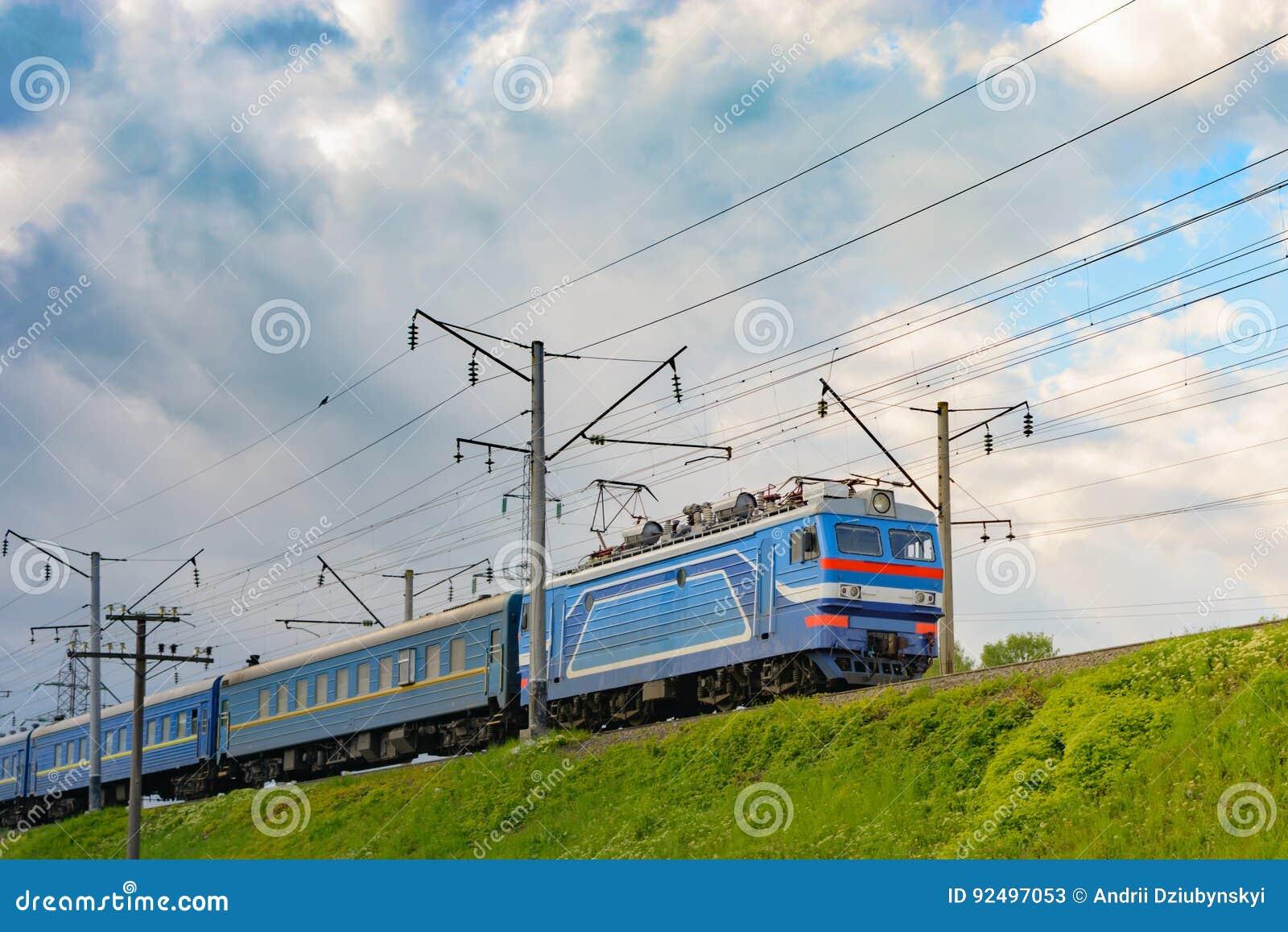 Le train de voyageurs monte sur une ligne électrifiée contre un ciel bleu
