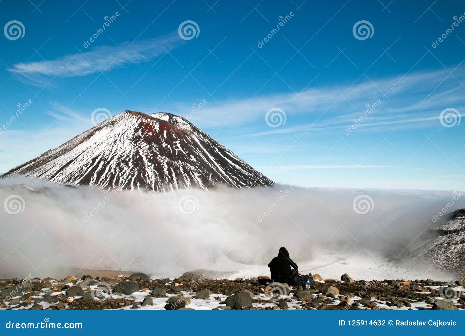 Le Tramper ayant le repos devant le volcan actif, le randonneur de montagne et le grimpeur prenant le casse-croûte et apprécie la