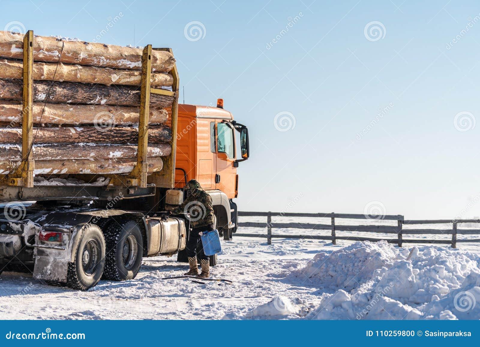Le transport de camion d arbres garé sur la neige, avec le conducteur ajoutent le carburant en hiver