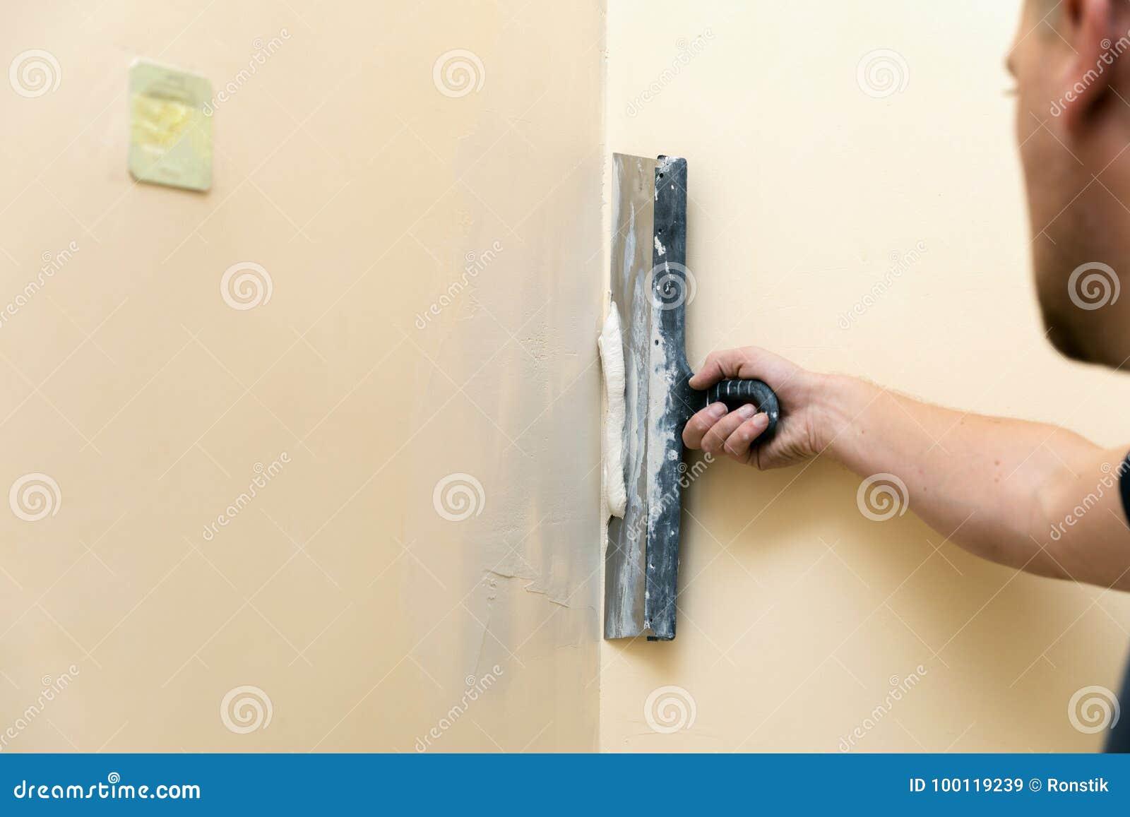 Le travail aligne - le travailleur plâtrant le mur avec la spatule