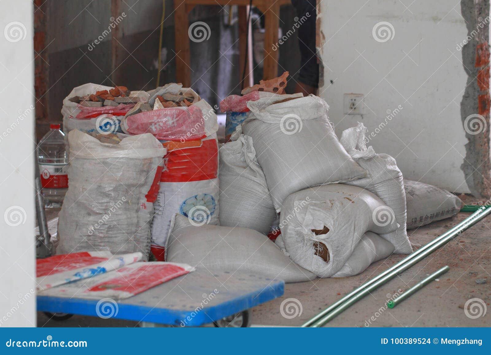 Le travail de rénovation électrique, de pleins débris de déchets de construction met en sac