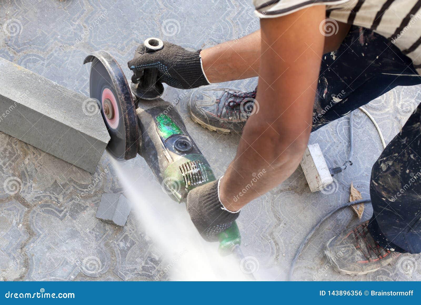 Le travailleur au chantier de construction scie un morceau de restriction concr?te avec la broyeur d angle, la scie ?lectrique ci