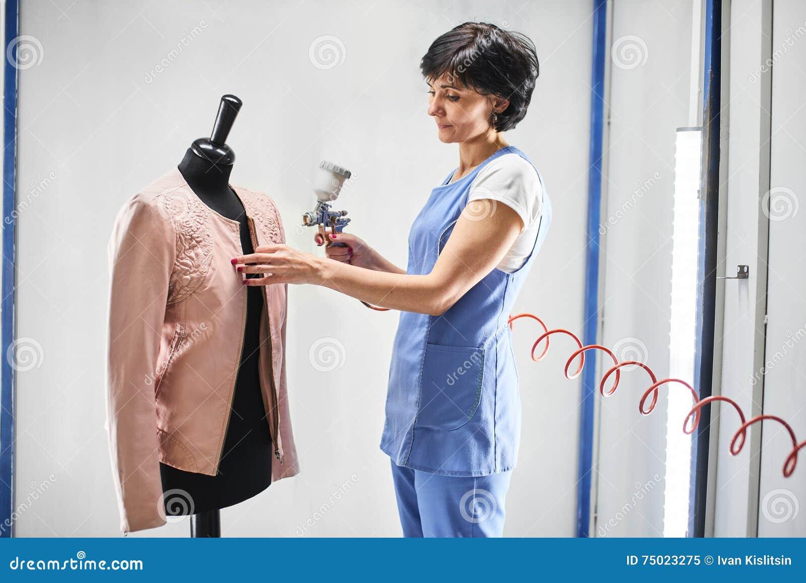 Le travailleur de blanchisserie de fille exécute les vestes en cuir de peinture sur un mannequin