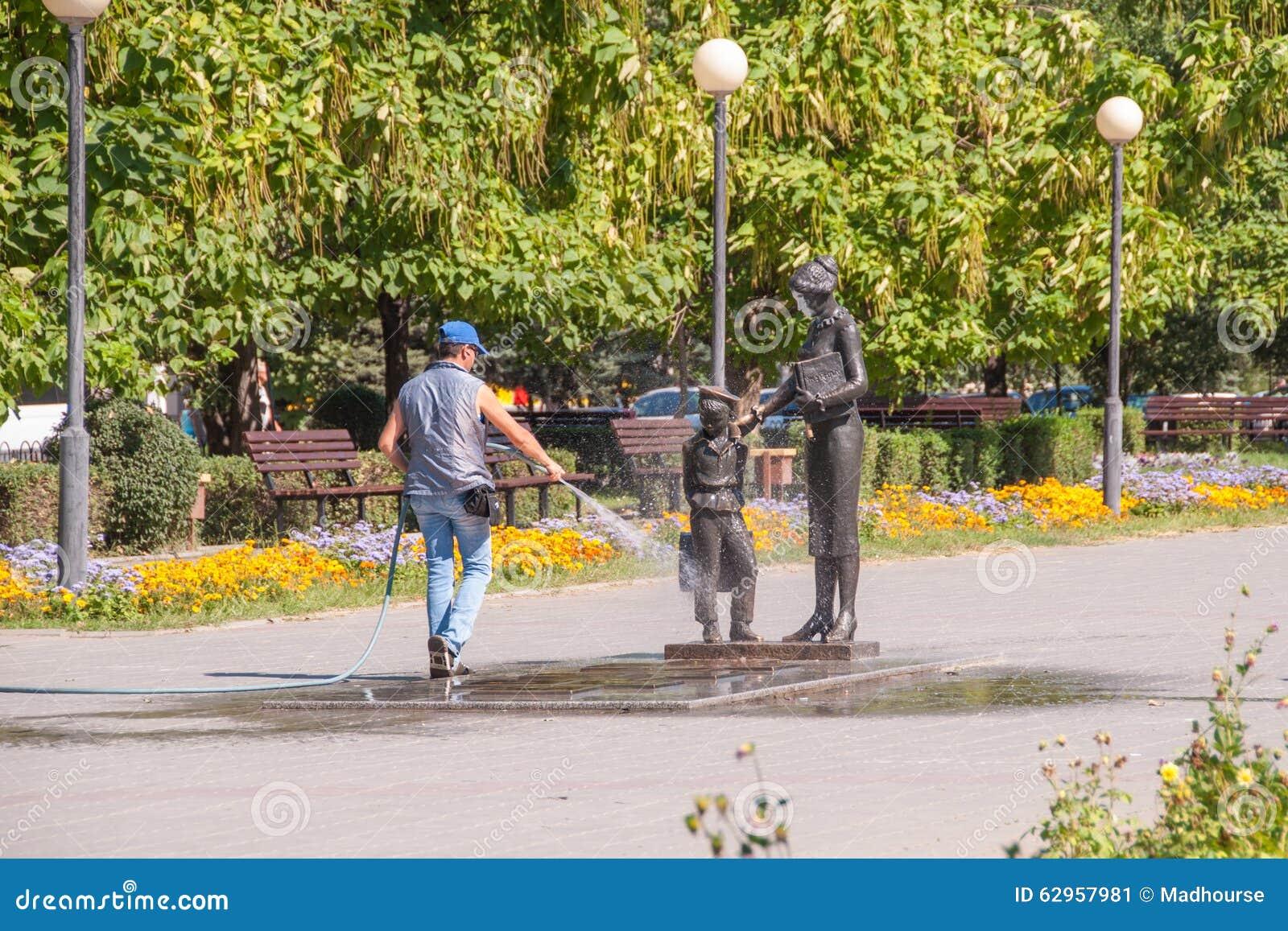 Le travailleur du logement et des services communaux lave avec de l eau du monument de tuyau au premier professeur Volgograd