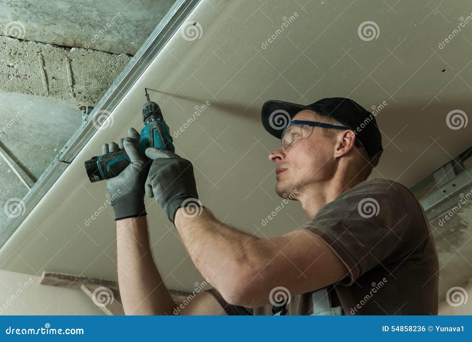 Le travailleur fixe la cloison sèche