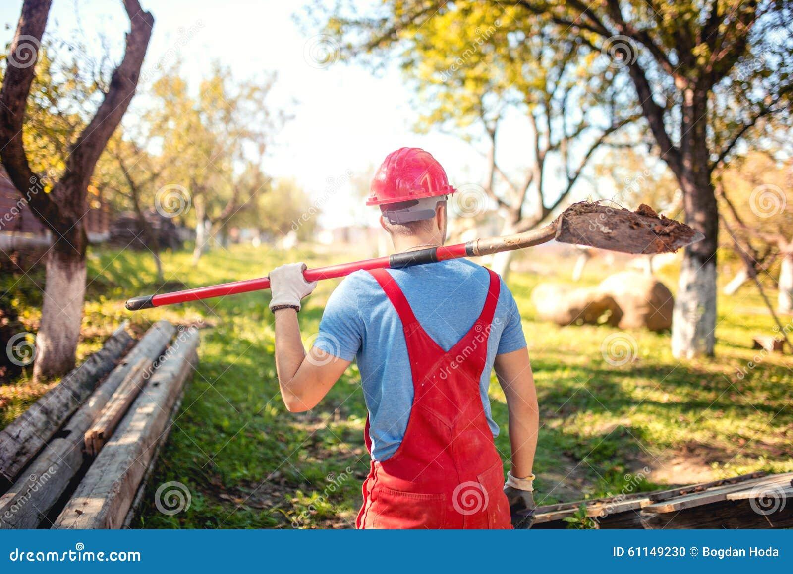 Le travailleur industriel avec le casque et le travail portent utilisant une pelle pour creuser un tunnel concept d agriculture a