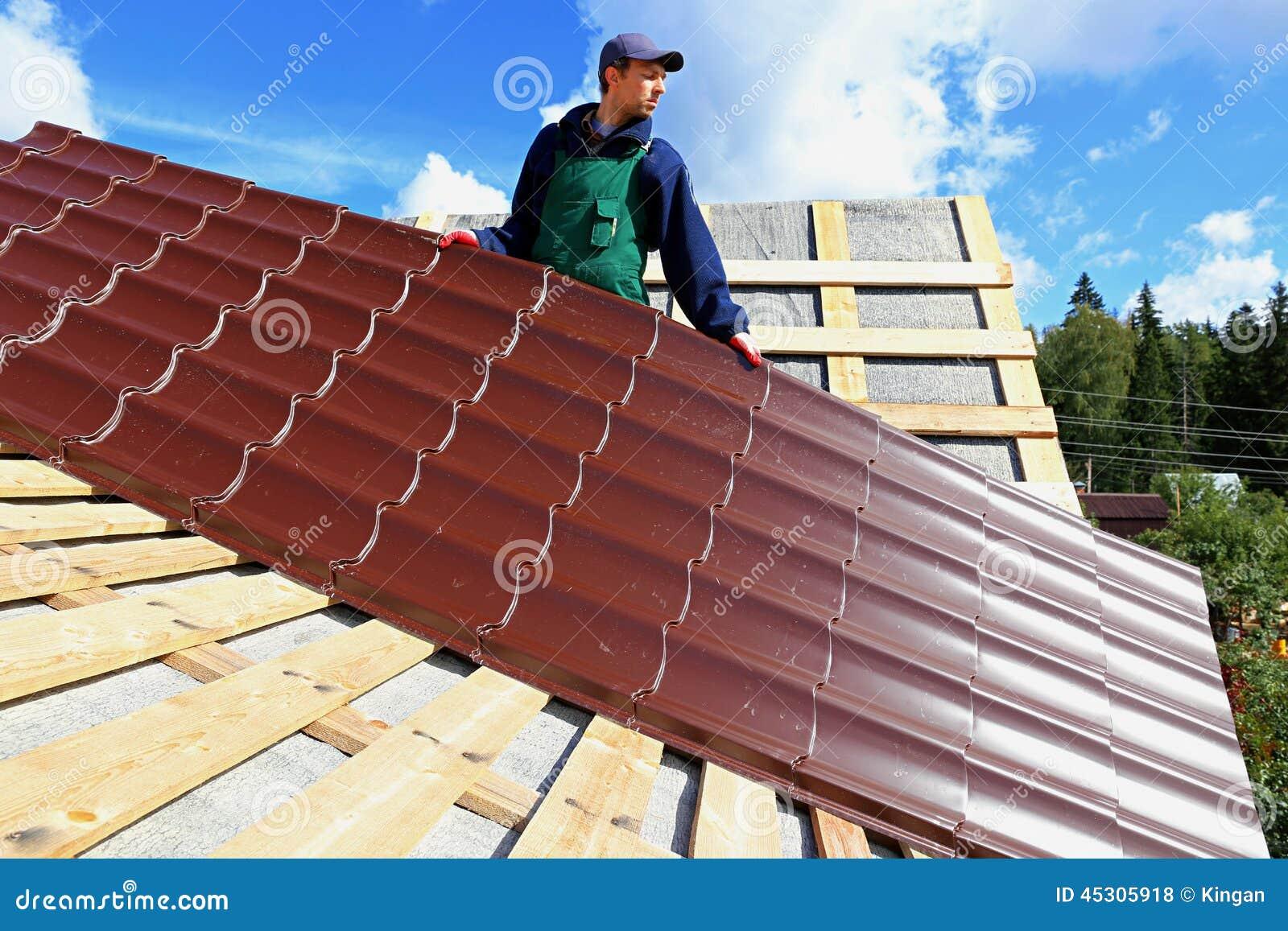 le travailleur met les tuiles en m tal sur le toit photo. Black Bedroom Furniture Sets. Home Design Ideas