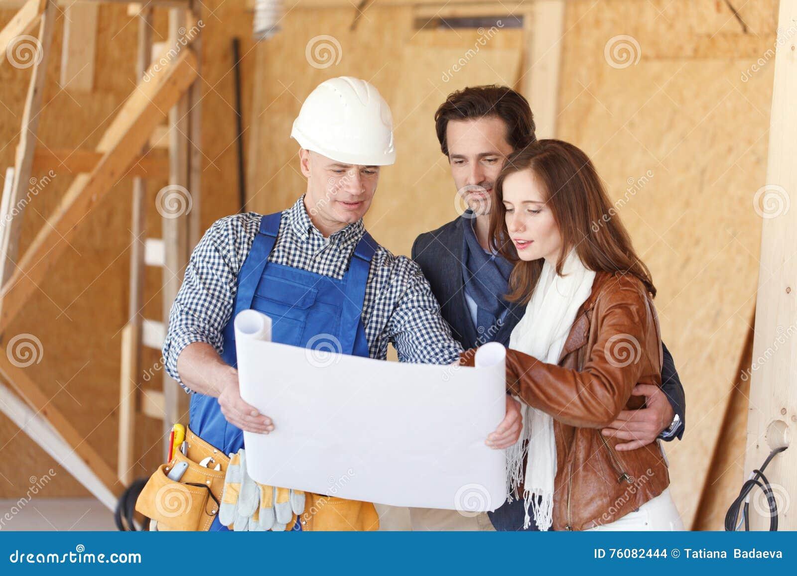 Le travailleur montre des plans de développement de maison