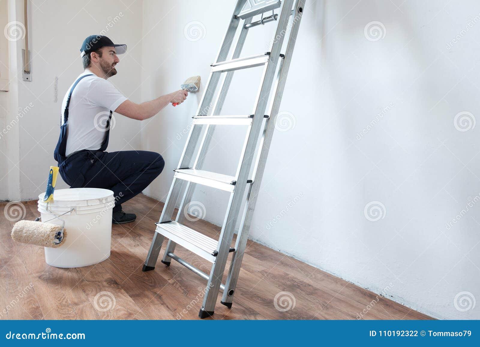 Le Travailleur Professionnel De Peintre Peint Un Mur Photo Stock