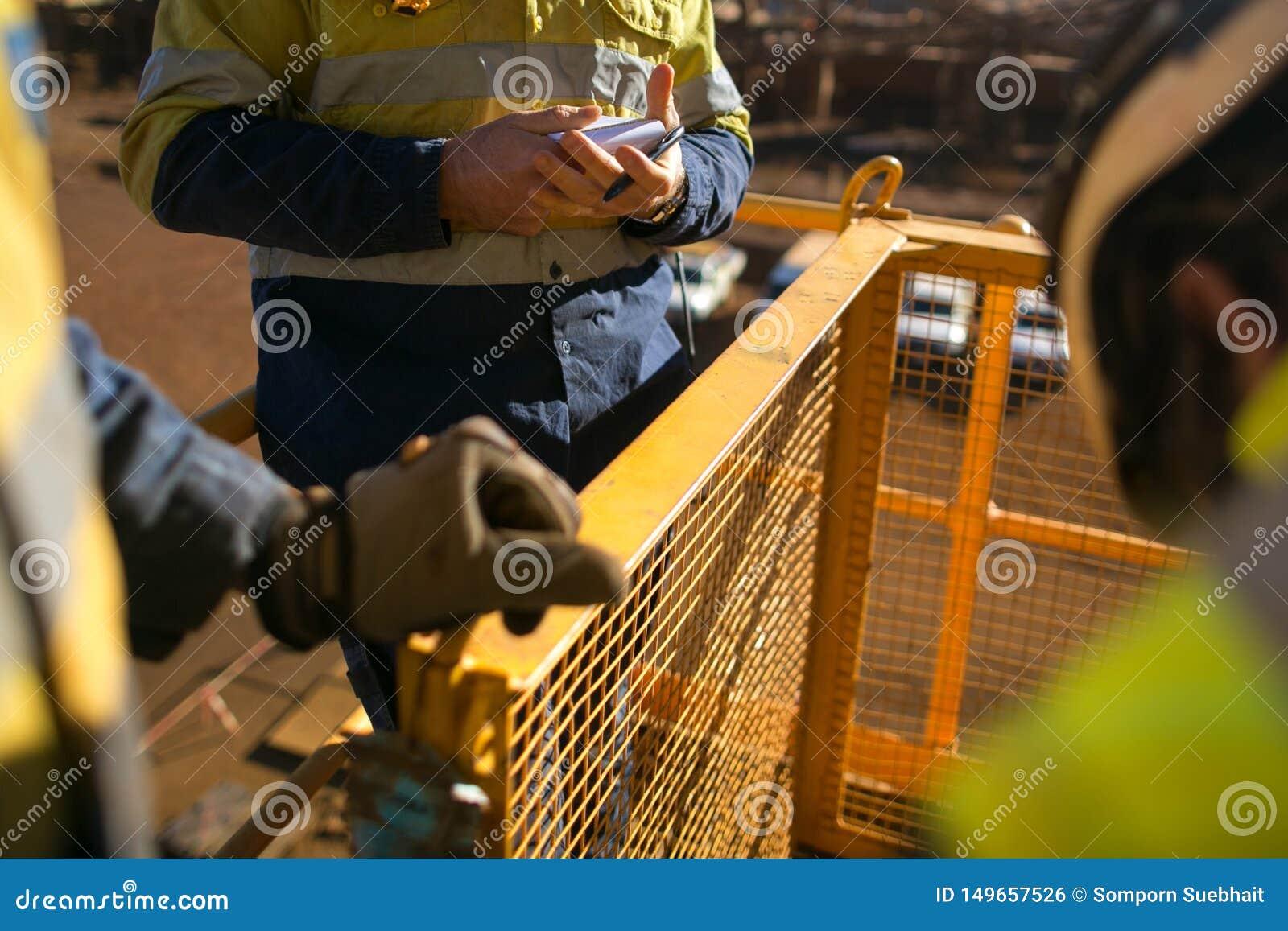 Le travailleur regardant l ?valuation des risques de personnel prennent le livre cinq ? la construction