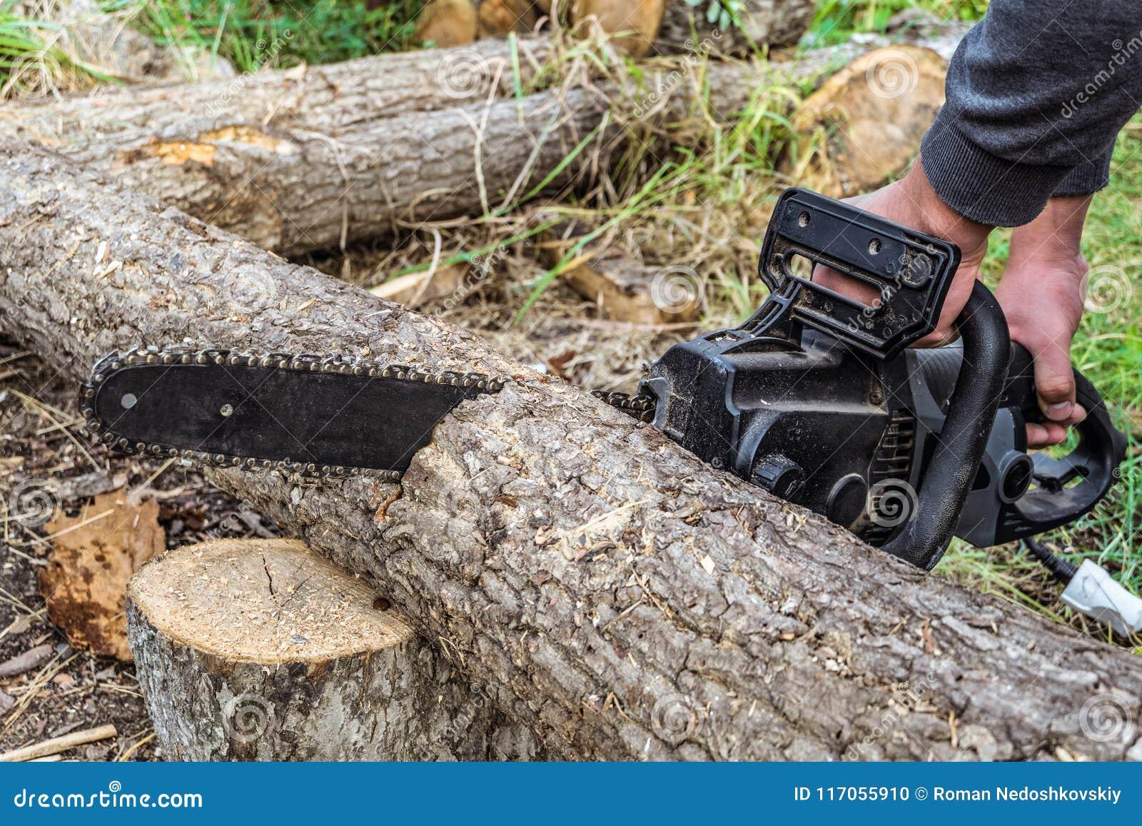 Le travailleur scie un rondin en bois avec la tronçonneuse électrique