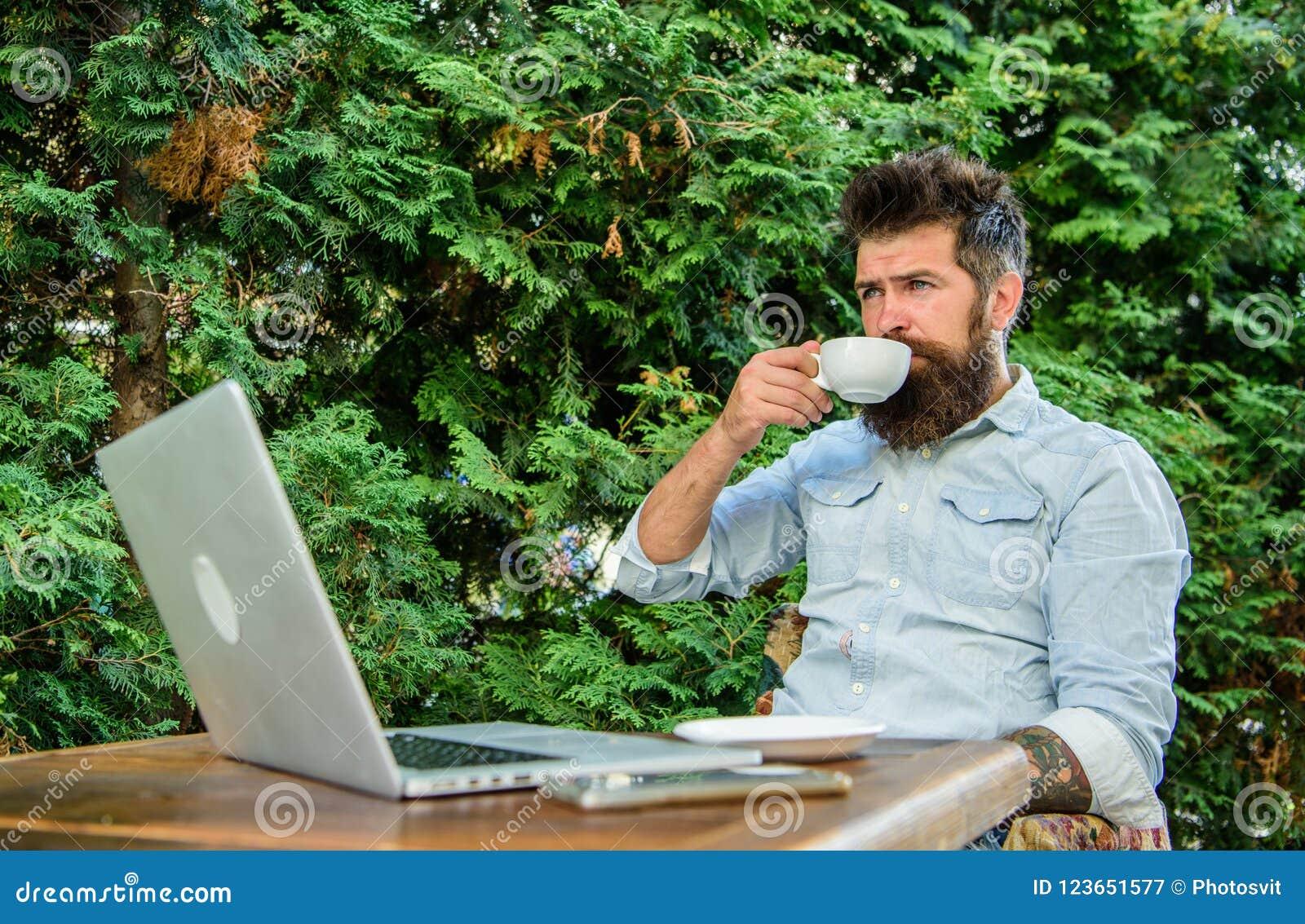 Le type boit le fond de détente de branches de terrasse de café Équipez le hippie barbu font la pause pour le café de boissons et