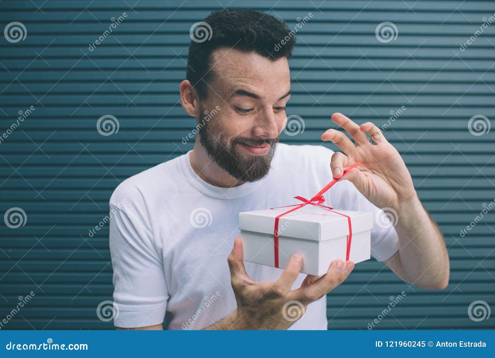 Le type délicieux et gentil ouvre la boîte actuelle Il regarde l irt et retire le ruban rouge Il est très enthousiaste