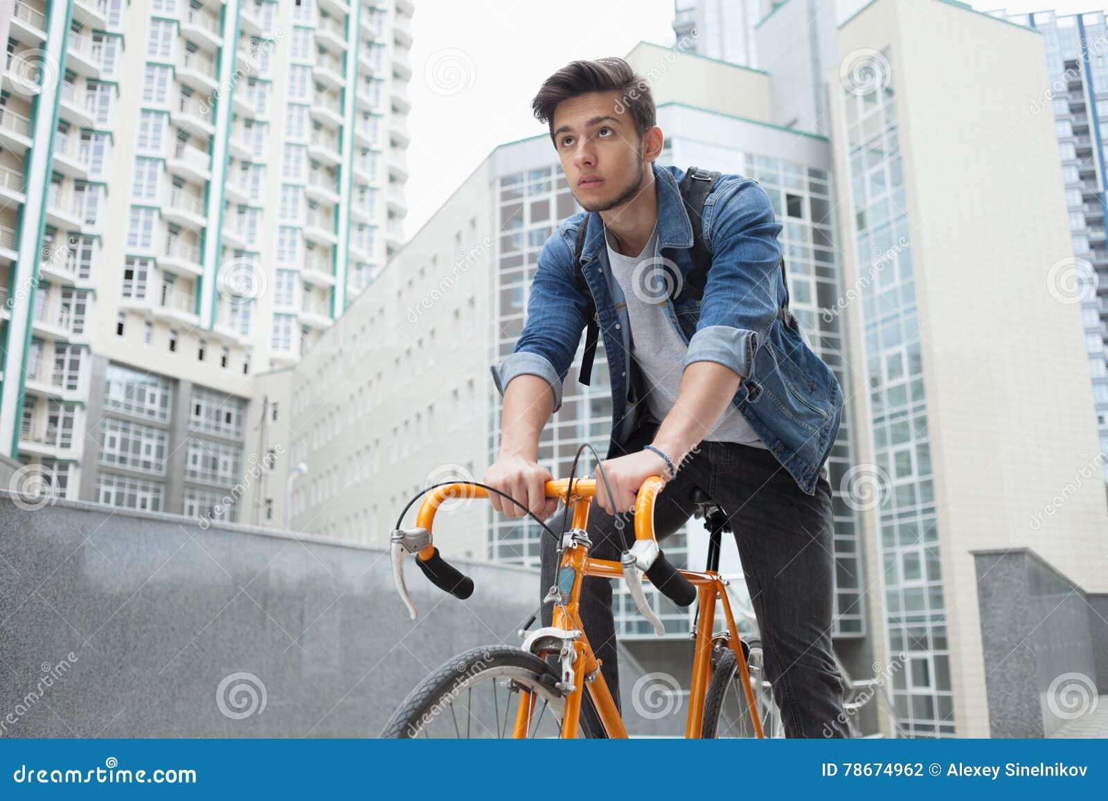 Le type va à la ville sur une bicyclette dans la veste de blues-jean jeune homme un vélo orange de difficulté