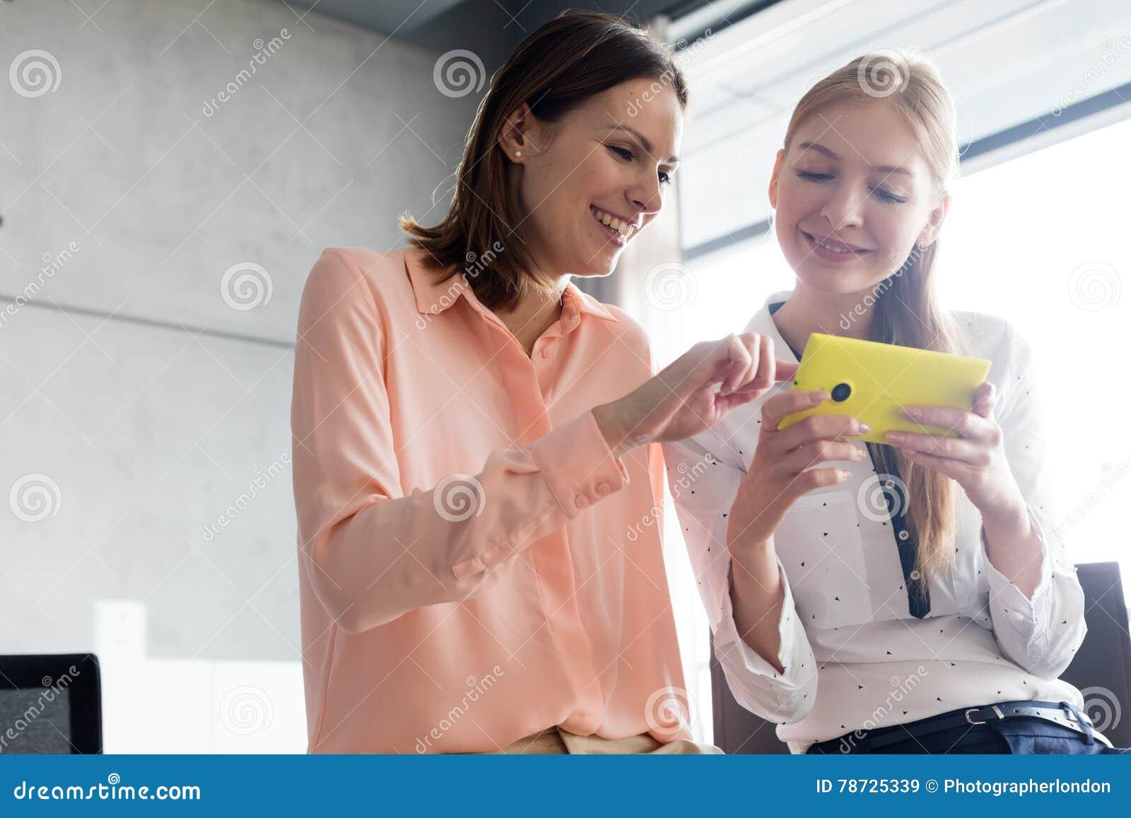 Le unga affärskvinnor som i regeringsställning använder mobiltelefonen