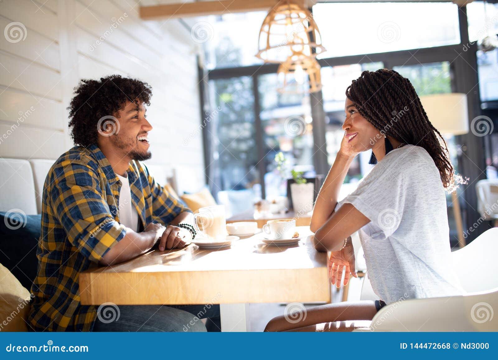 Le unga afrikanska par som sitter på en tabell på ett kafé som dricker kaffe och tillsammans talar