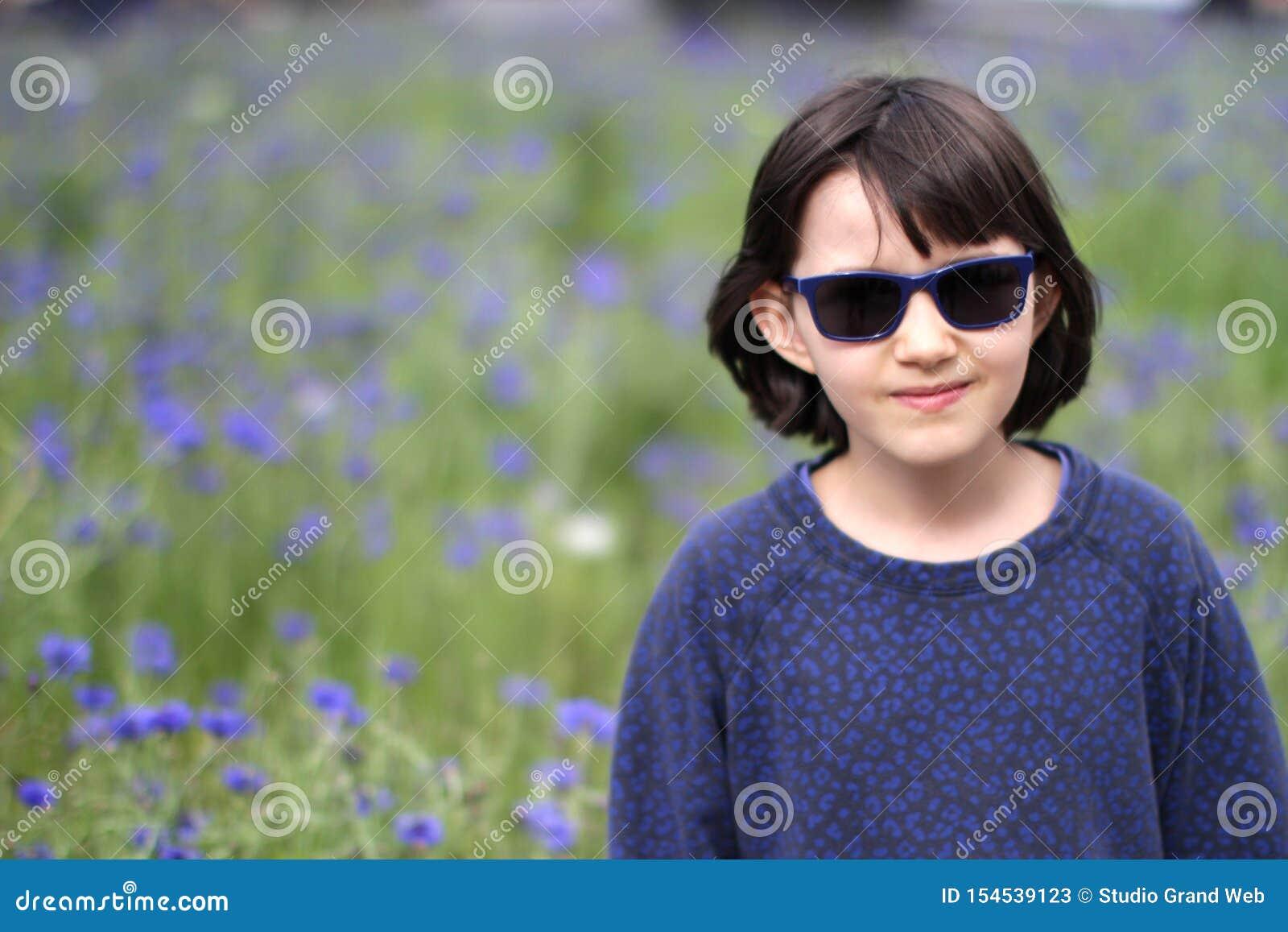 Le unga barnet med solglasögon som går över suddig blåklintträdgård