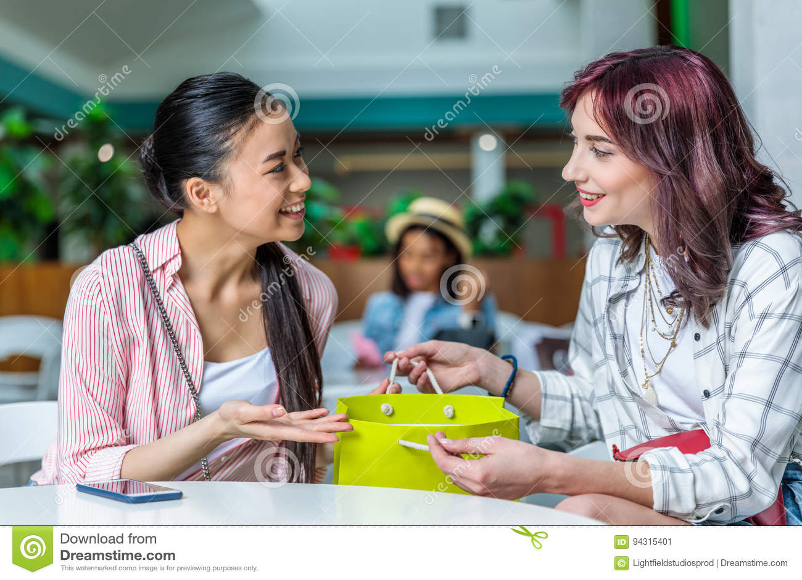 Le unga kvinnor med shoppingpåsen som tillsammans sitter och samtal