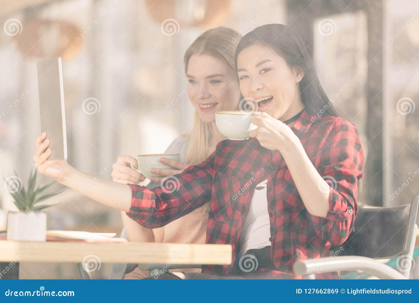 Le unga kvinnor som dricker kaffe och att använda digitalt kaffe för minnestavla tillsammans