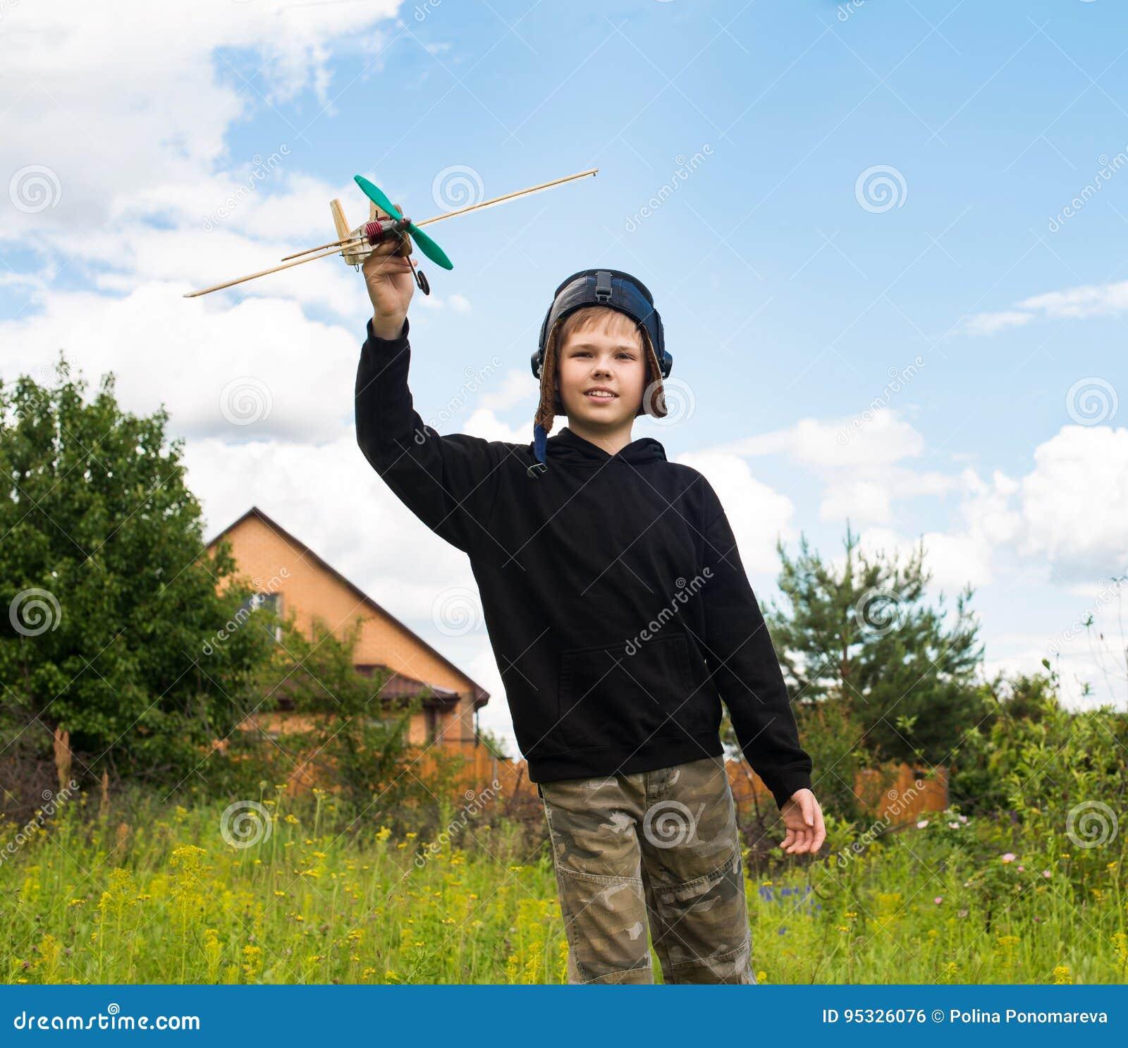 Le ungen i pilot- hjälm med den plana modellen utomhus dröm