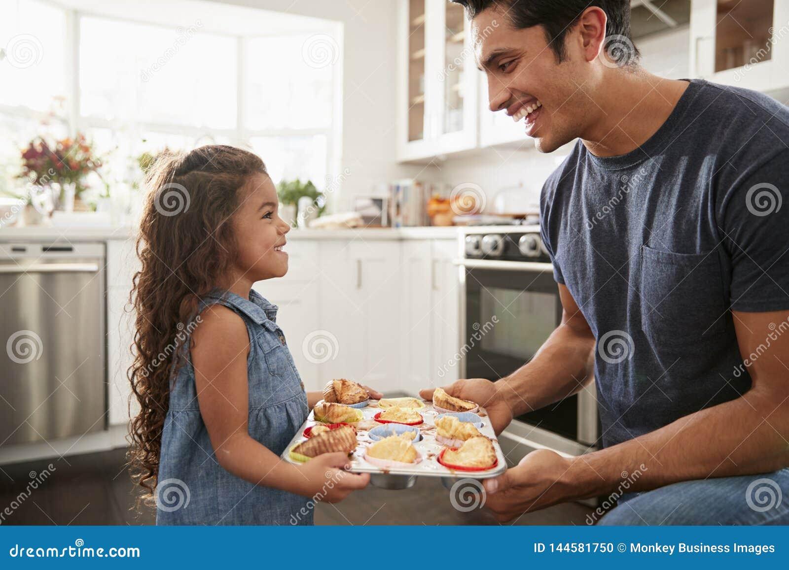 Le ungt latinamerikanskt flickaanseende i kök som framlägger kakorna har hon, bakat till hennes fader