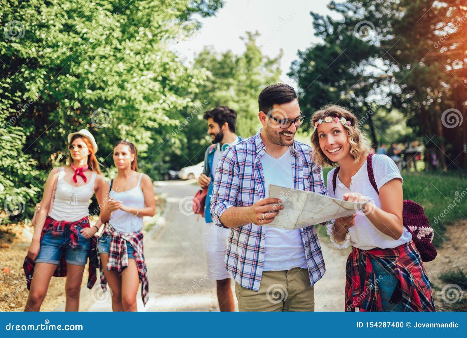 Le vänner som går med ryggsäckar i trän - affärsföretag, lopp, turism, vandring och folkbegrepp