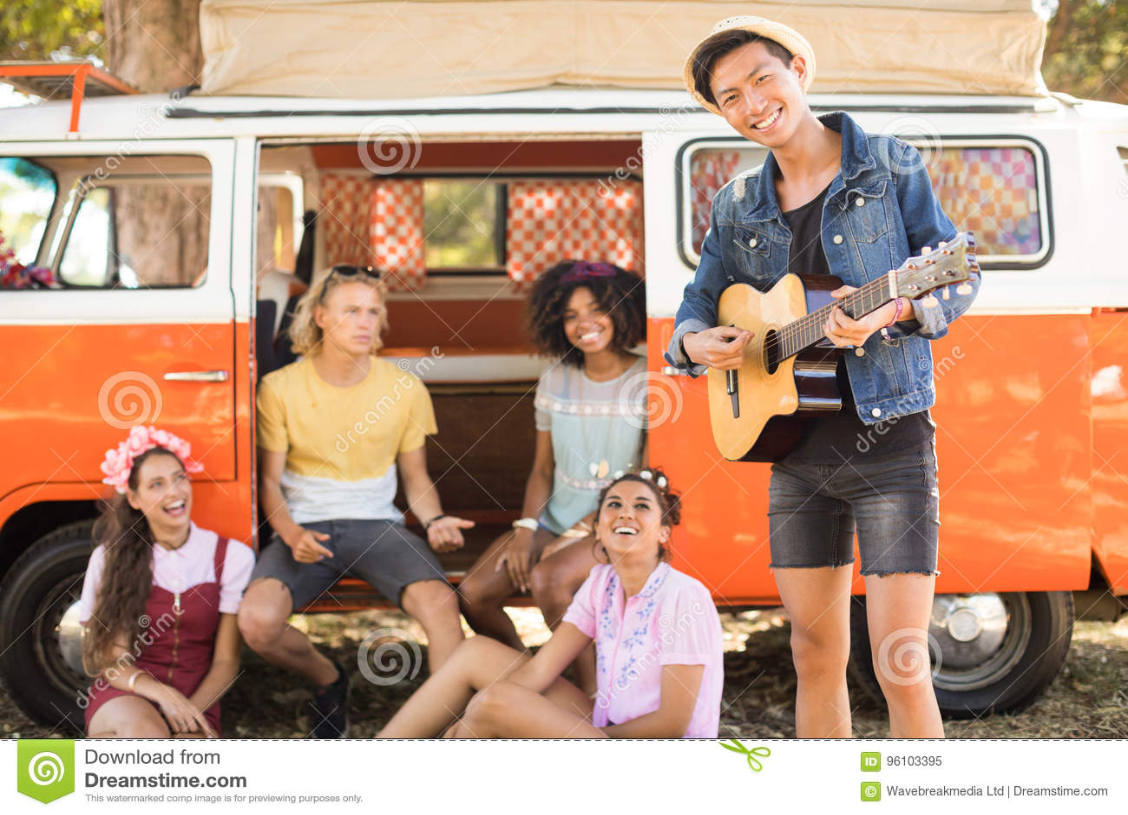 Le vänner som ser mannen som spelar gitarren