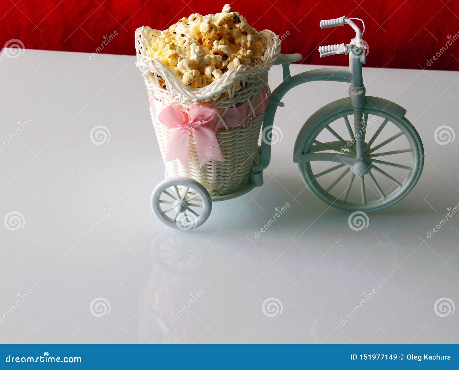 Le vélo décoratif porte le maïs éclaté dans un chariot