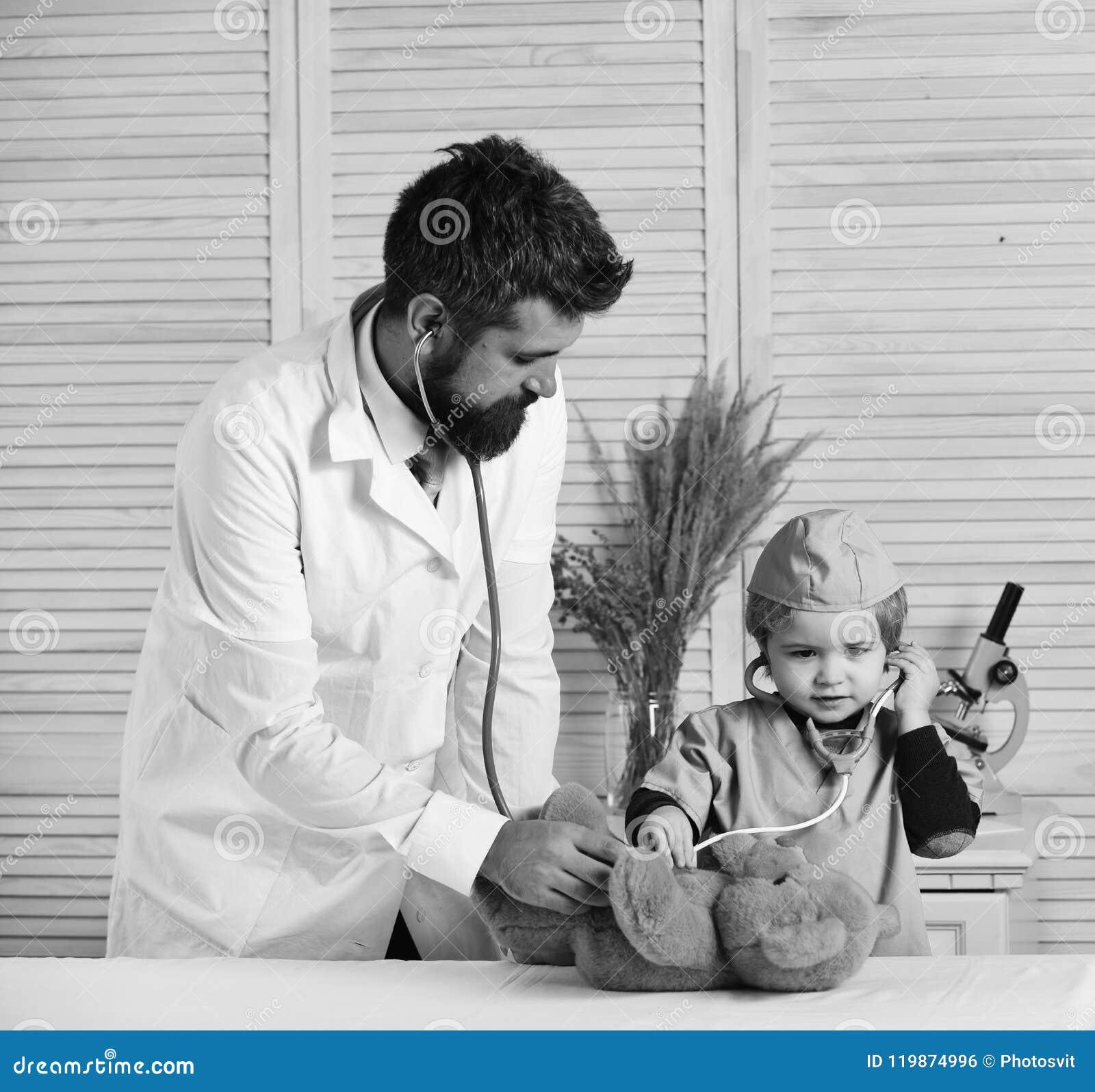 Le vétérinaire et le petit assistant examinent l ours de nounours Engendrez et badinez avec les visages attentifs jouant le docte