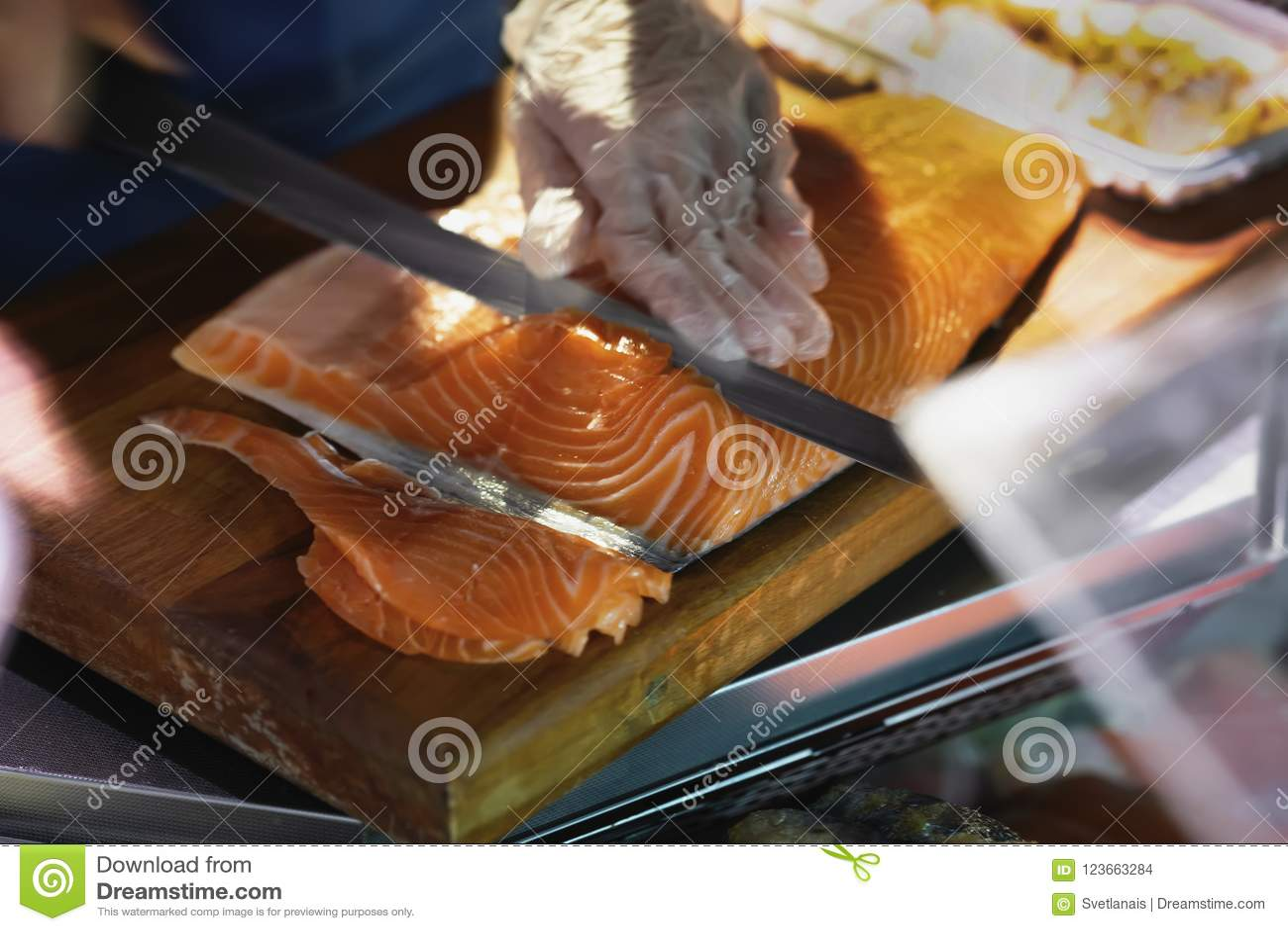 Le vendeur coupe et vend des saumons sur le panneau en bois du marché Mains avec le plan rapproché de couteau Produit gastronomiq