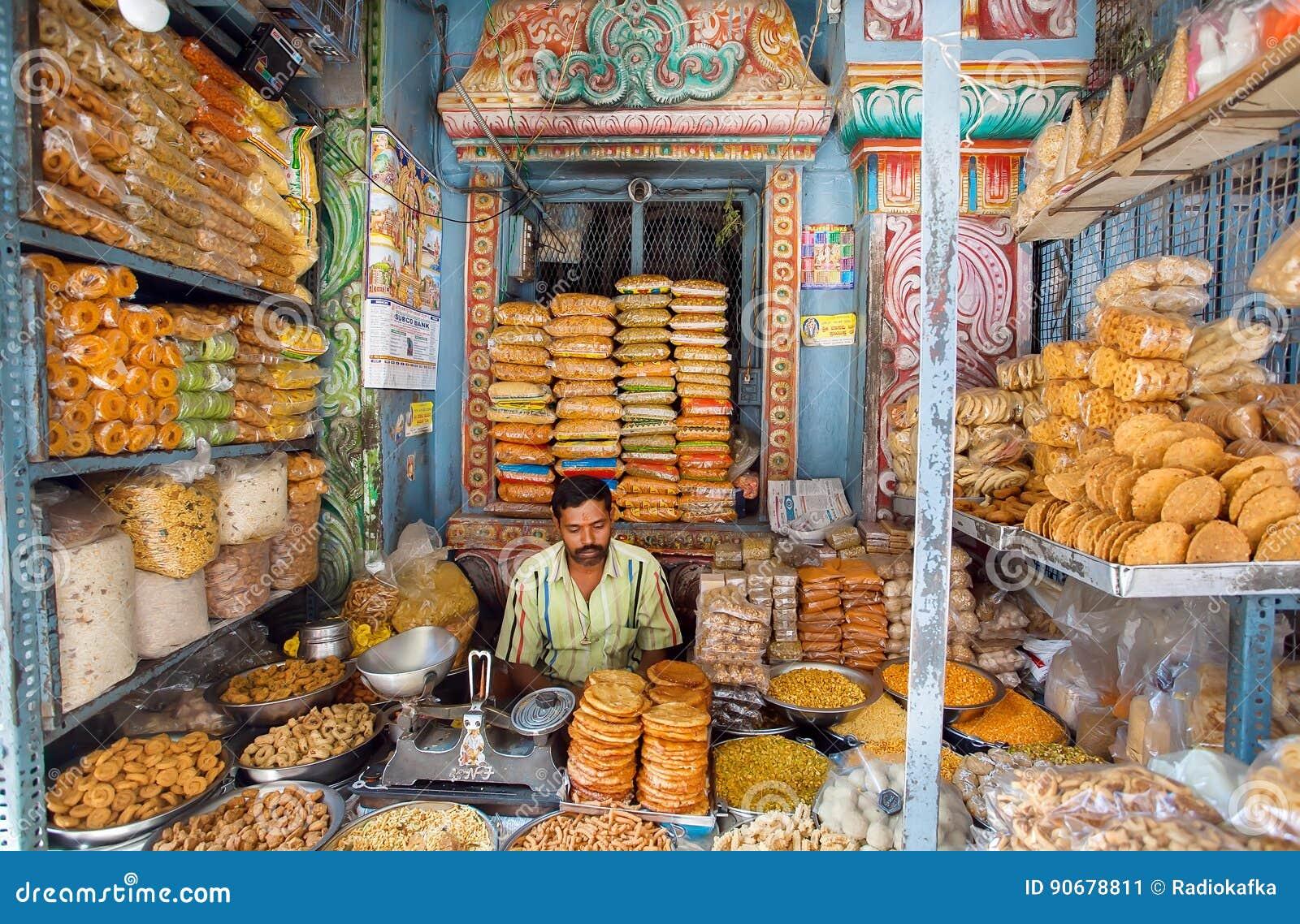 Le vendeur des bonbons attend des acheteurs dans une boutique colorée avec des biscuits et des casse-croûte