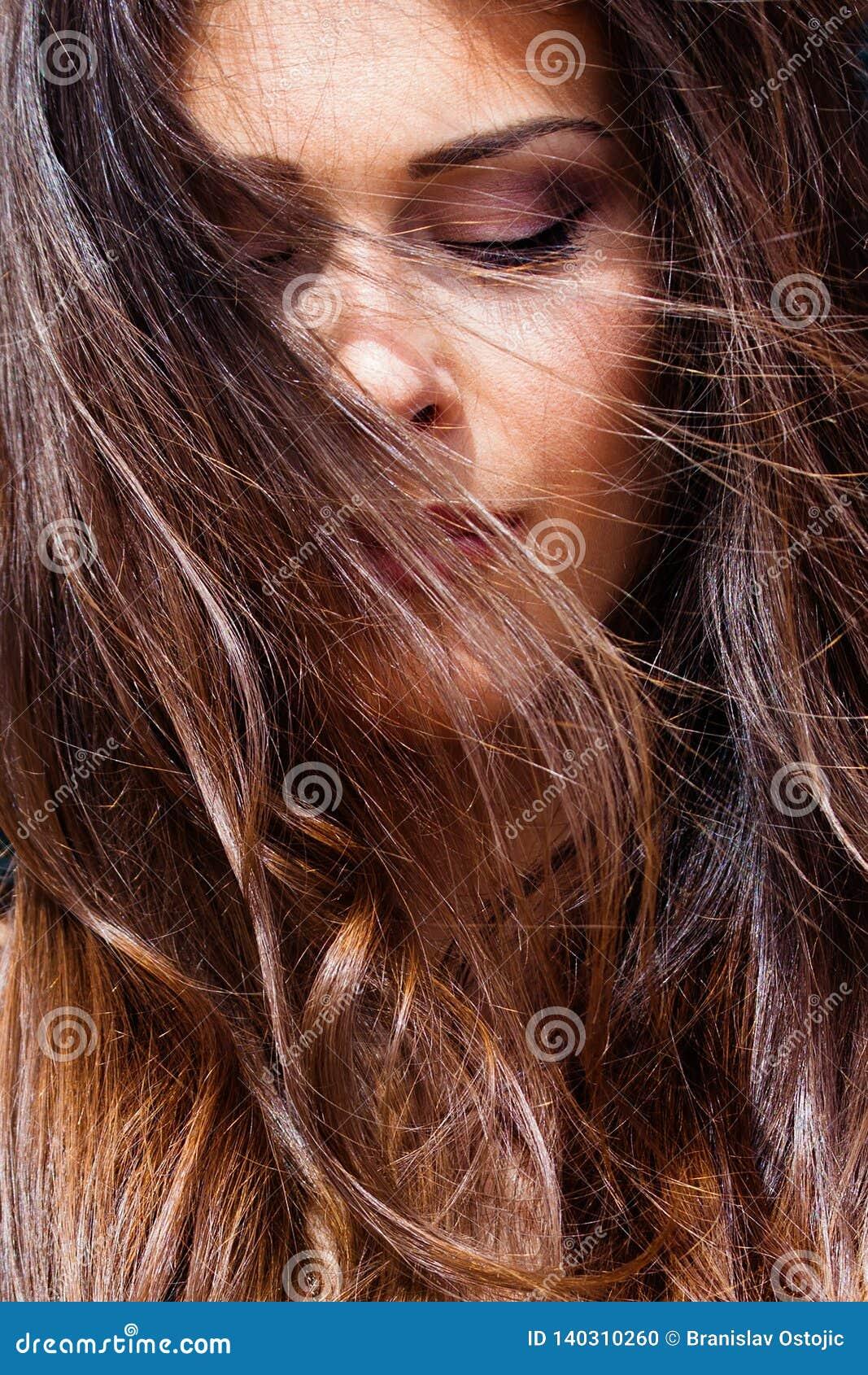 Le vent de portrait de jeune femme dans des yeux de cheveux a fermé le plan rapproché extérieur ensoleillé