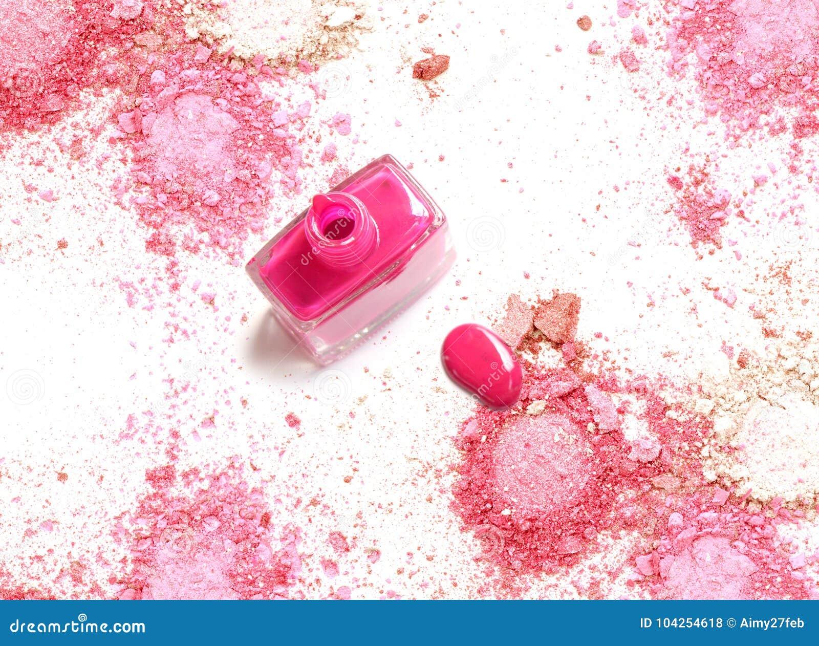 Le vernis à ongles rose sur la poudre rose écrasée composent
