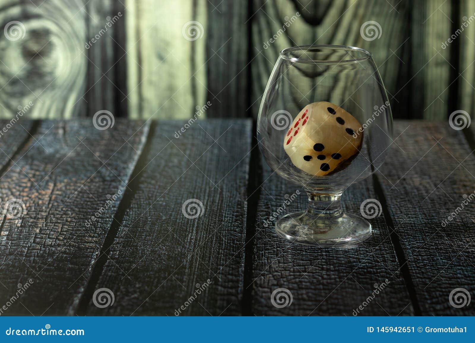 Le verre avec le cube en jeu se tient sur la table