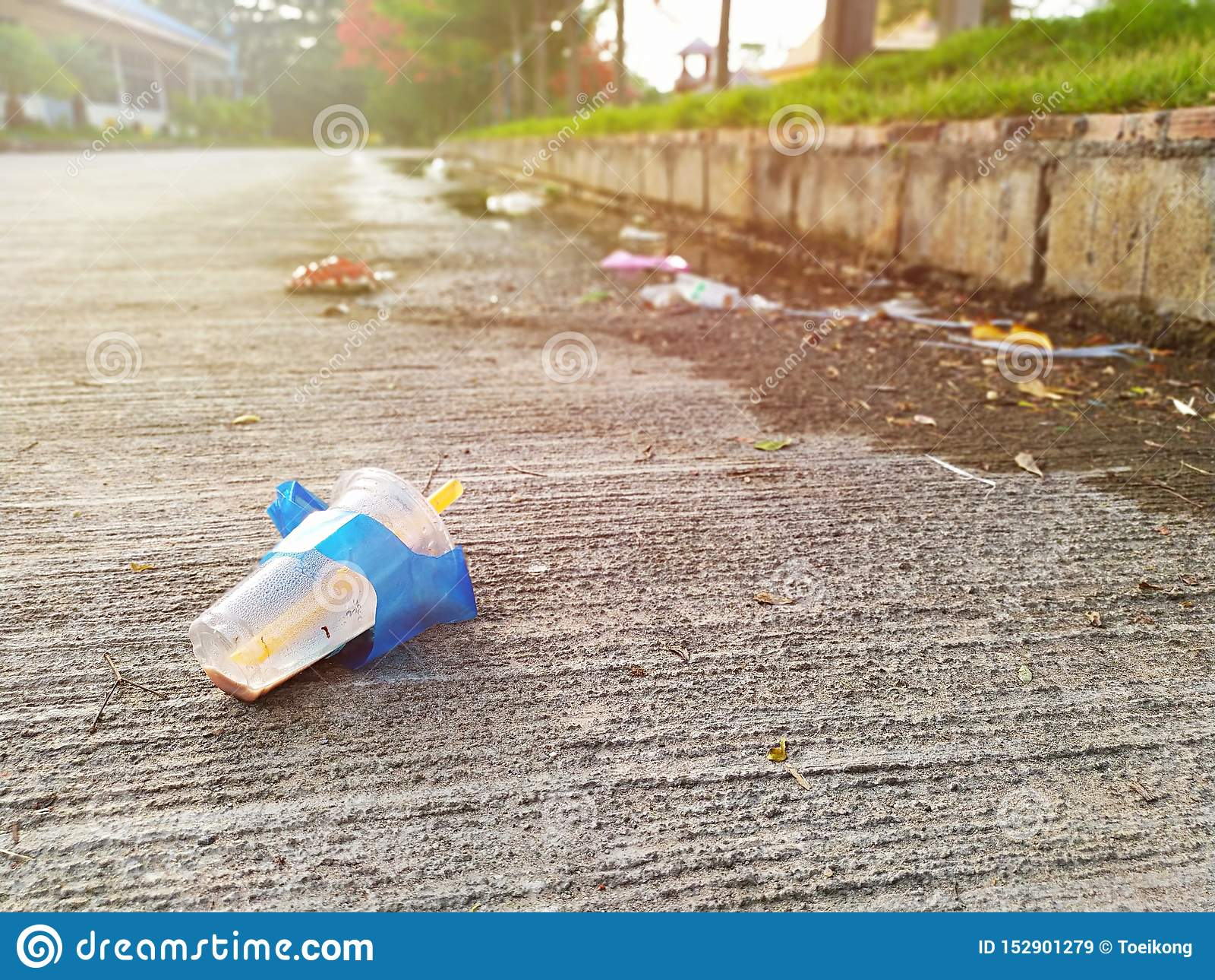 Le verre en plastique utilisé a été laissé comme déchets sur la rue