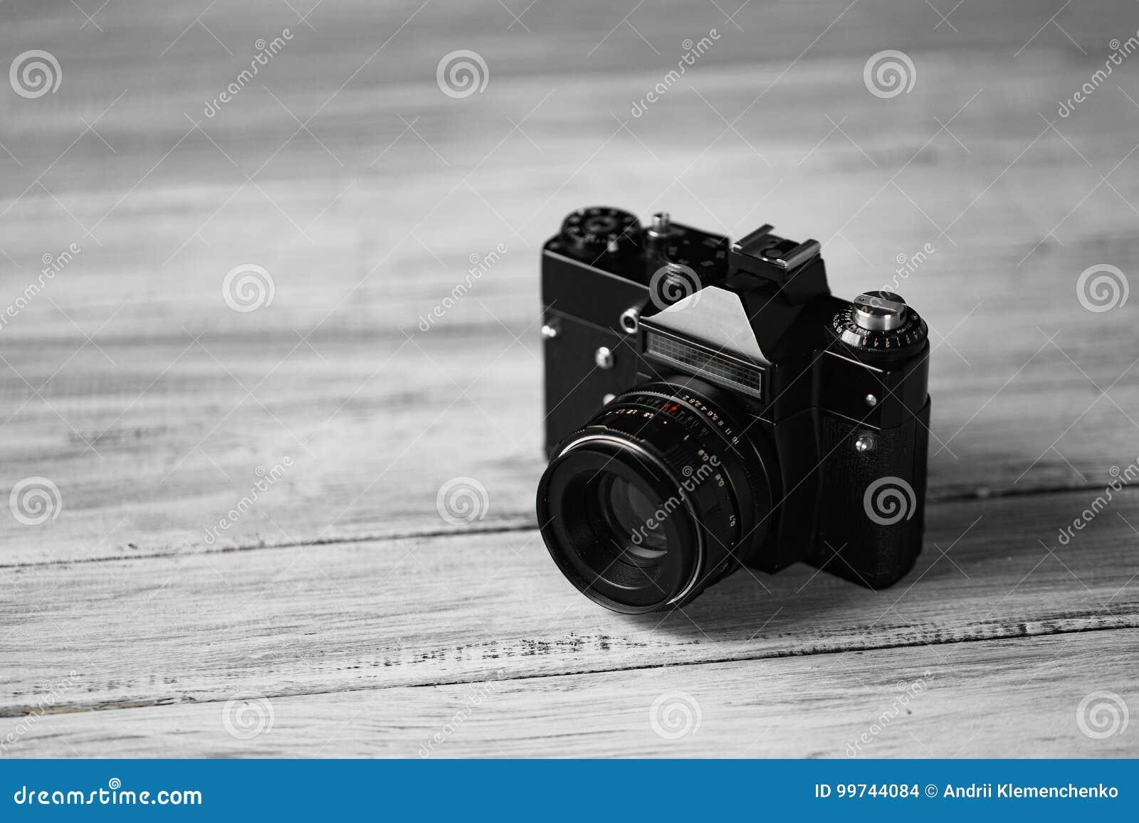 Le vieil appareil-photo manuel sur un fond blanc sur la table en bois Appareil-photo noir professionnel