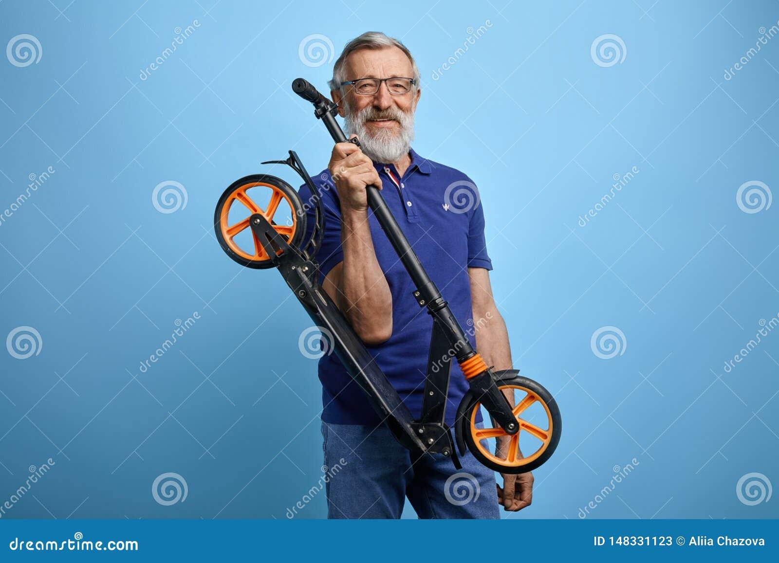 Le vieil homme beau actif dans des vêtements sport élégants va monter le scooter