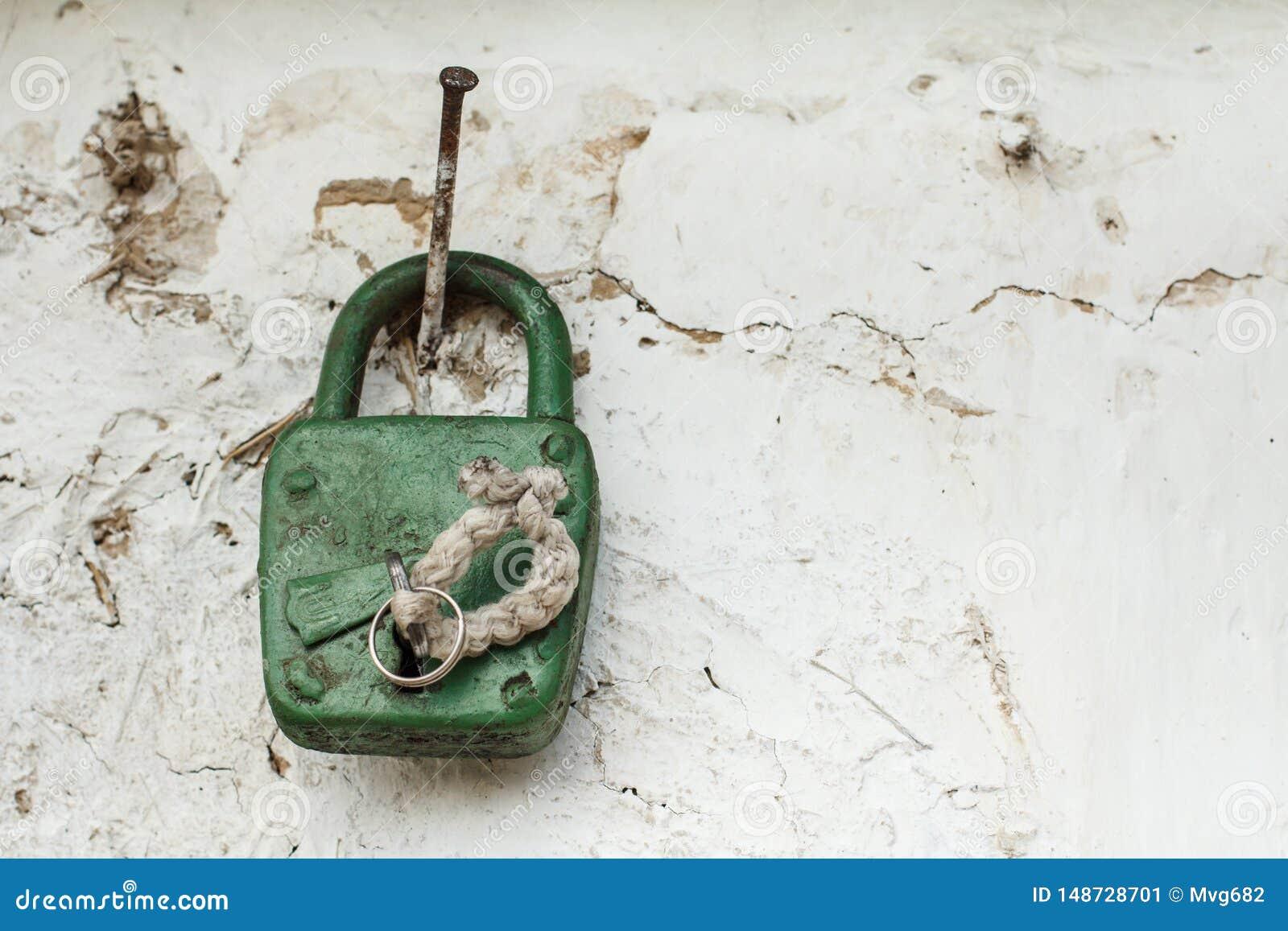 Le vieux cadenas accroche sur le clou martelé dans le vieux mur