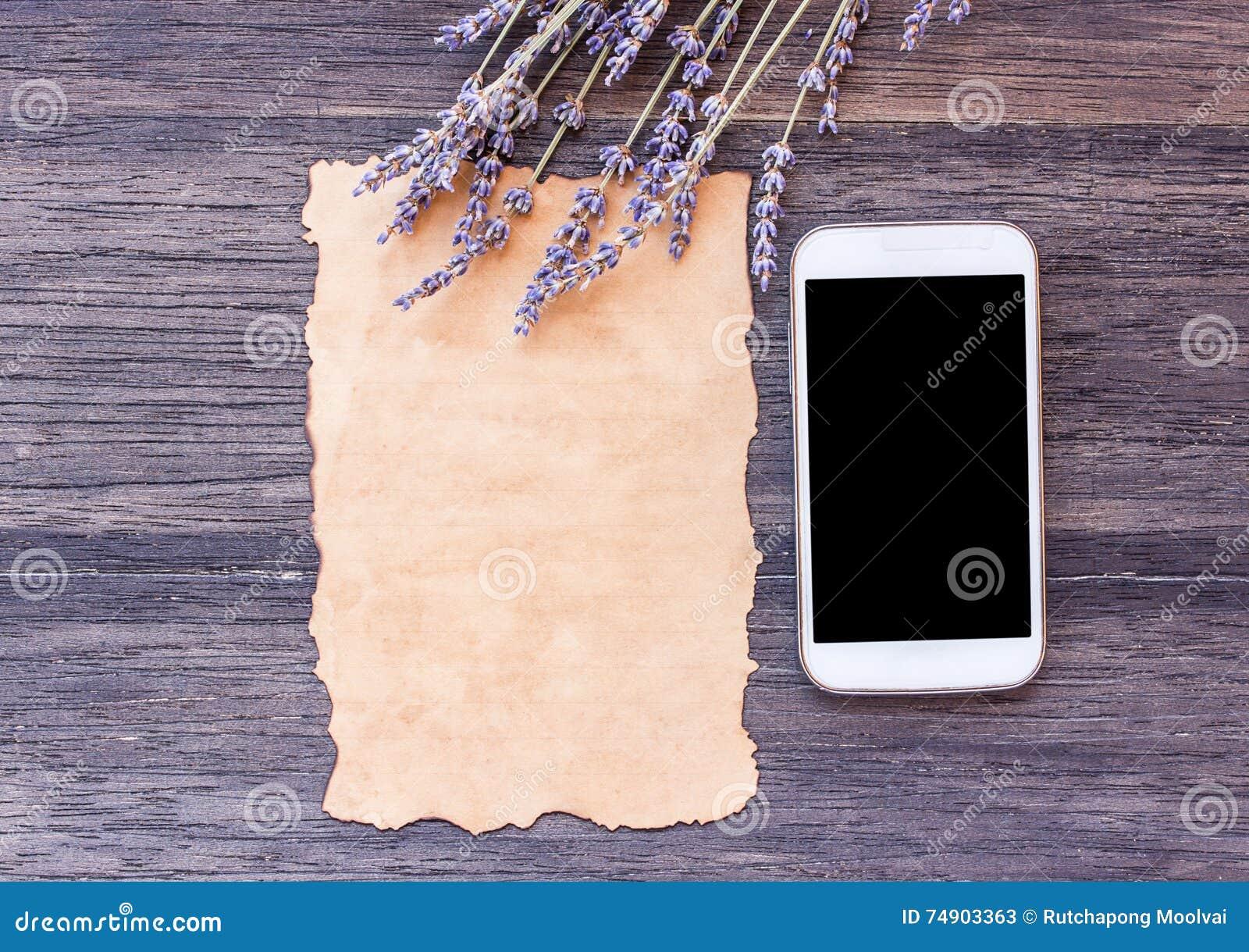Le vieux papier et le téléphone intelligent avec la lavande fleurissent sur en bois foncé merci