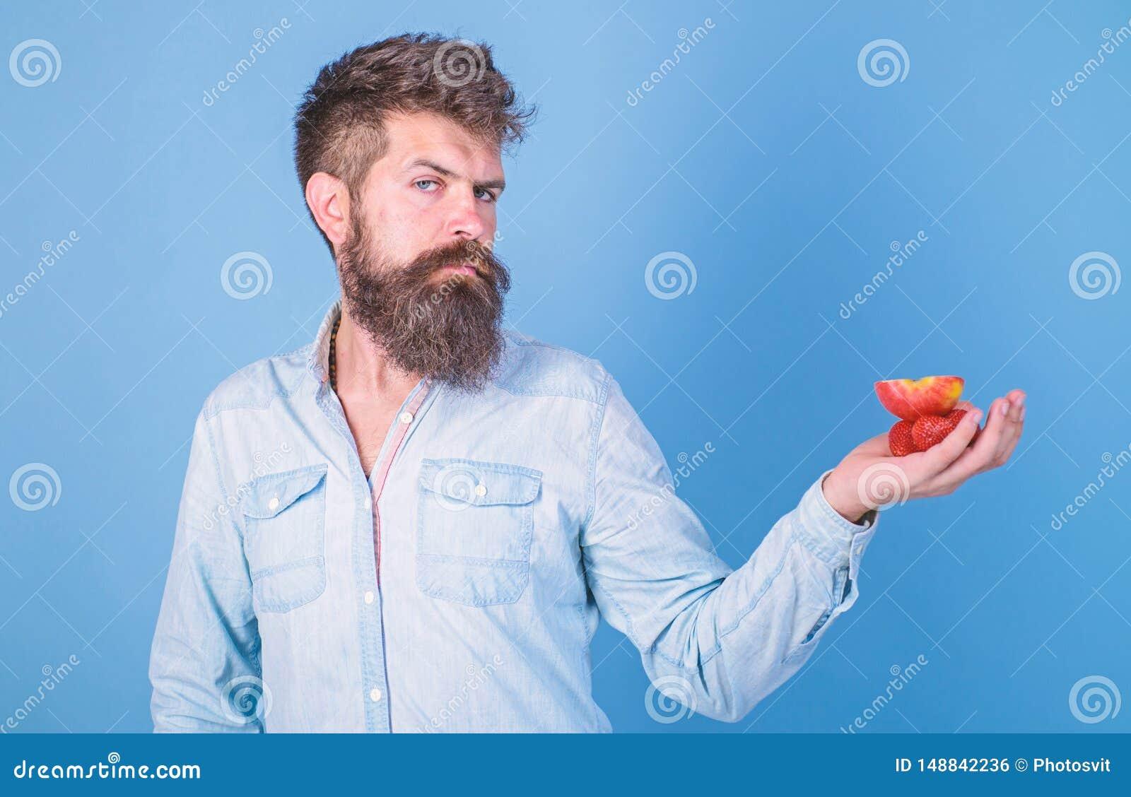 Le visage strict d homme avec la barbe offre les festins organiques Fraises et pomme barbues de prises de hippie sur la paume Off