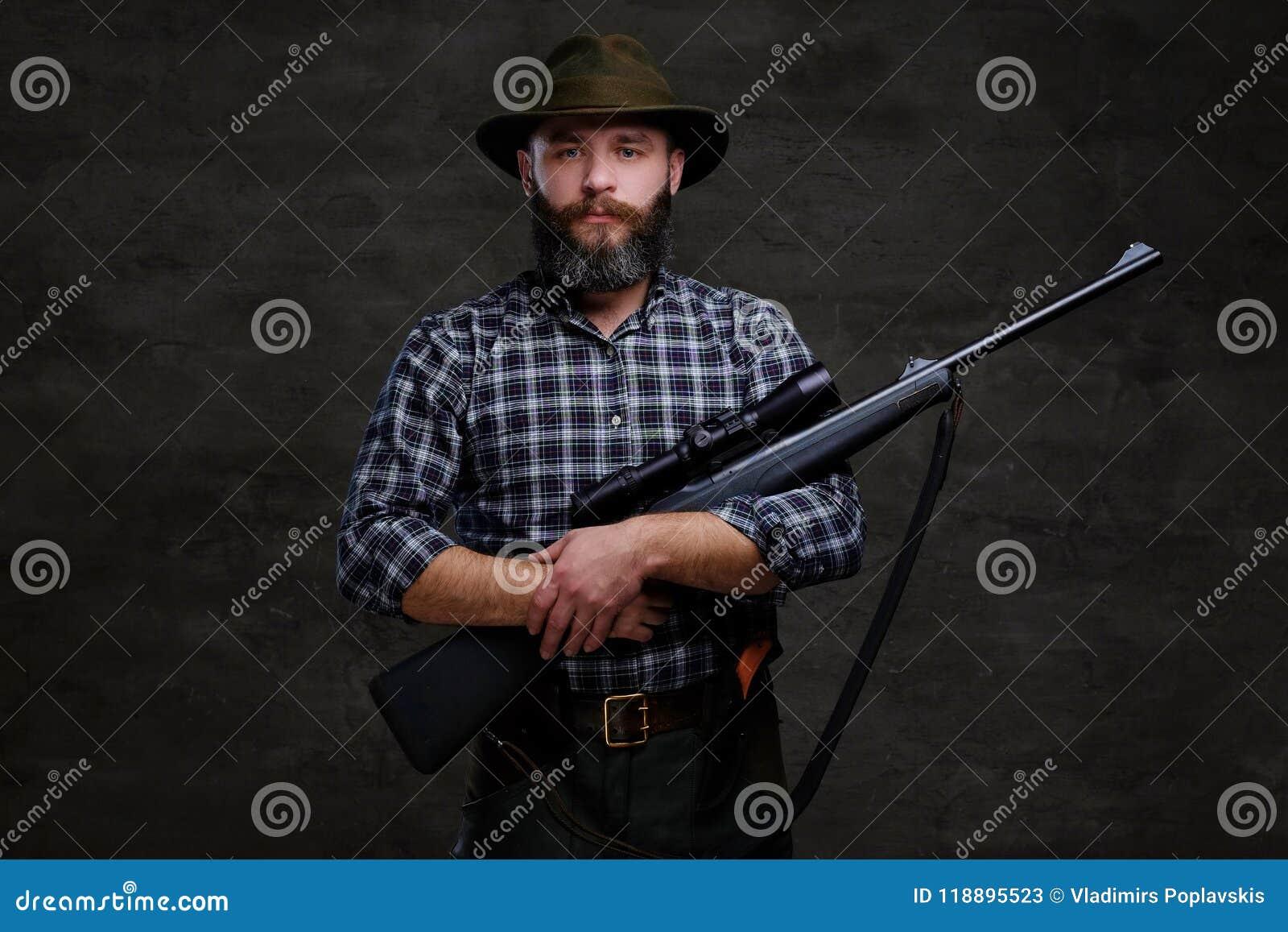 Le voyageur barbu beau de chasseur dans des prises d une chemise et de chapeau d ouatine fusillent avec une vue