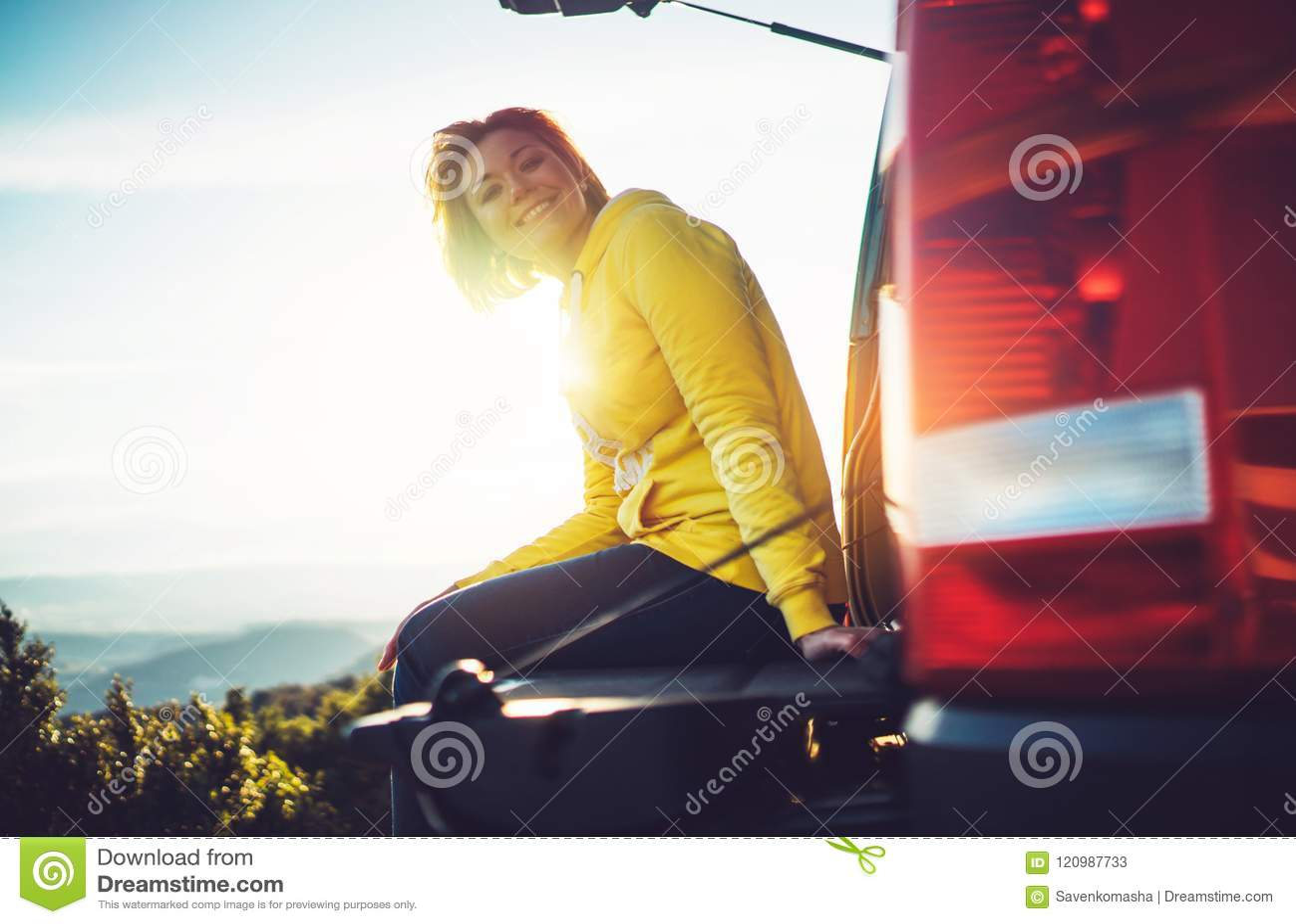 Le voyageur de touristes voyageant dans la voiture sur le dessus vert sur la montagne, jeune fille sourit heureusement contre le